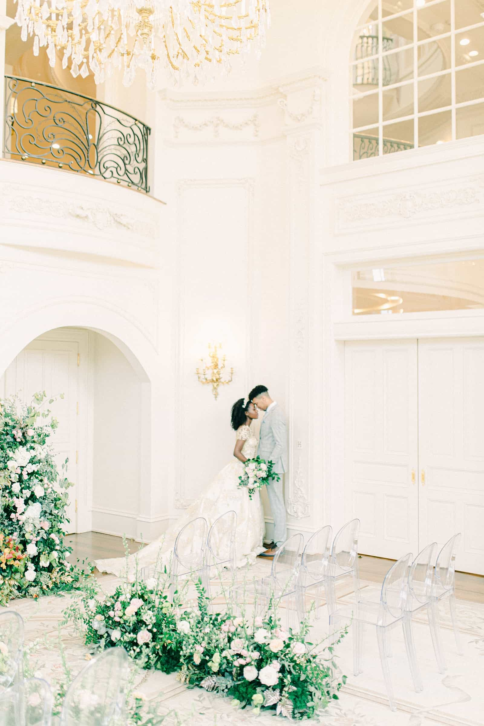 Disney princess bride and groom in all white ballroom, greenery and floral garland lining aisle, ceremony decor