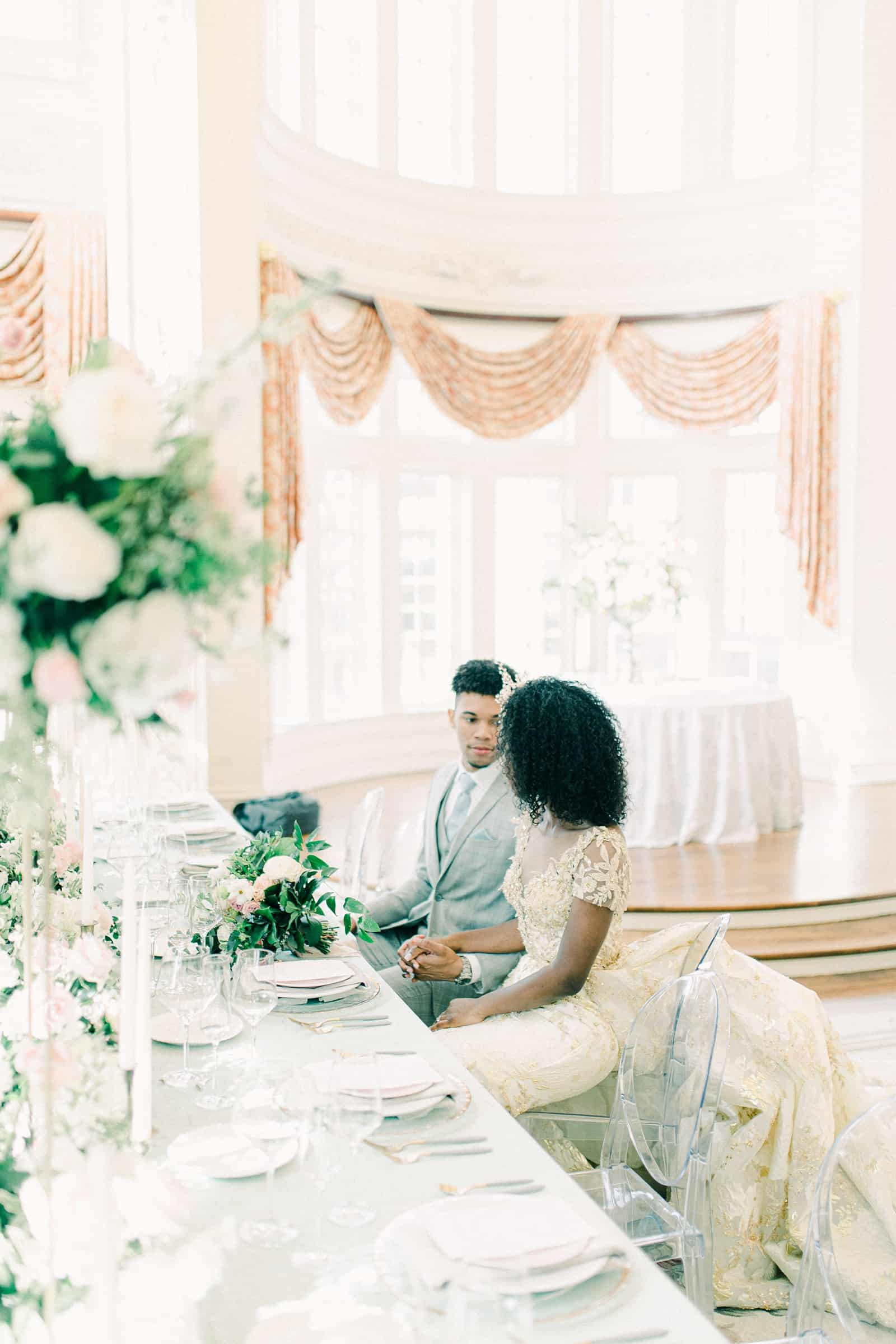 Bride and groom sitting at wedding dining table with light blue tablecloth, clear dining chairs, tall pink and white flower centerpieces, reception decor