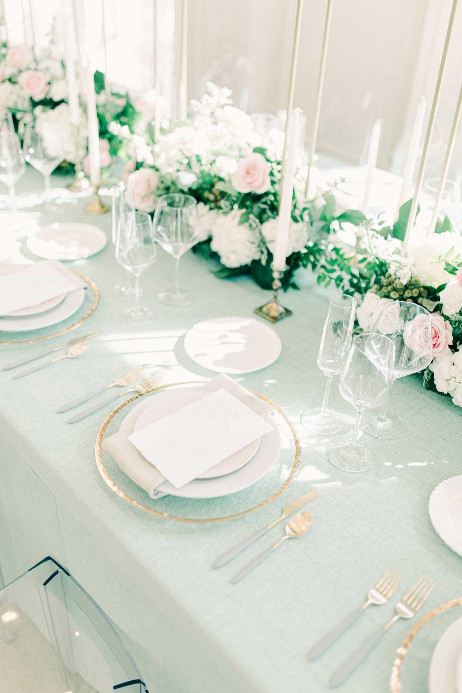 Wedding reception decor, gold rimmed dinner plates on light blue tablecloths
