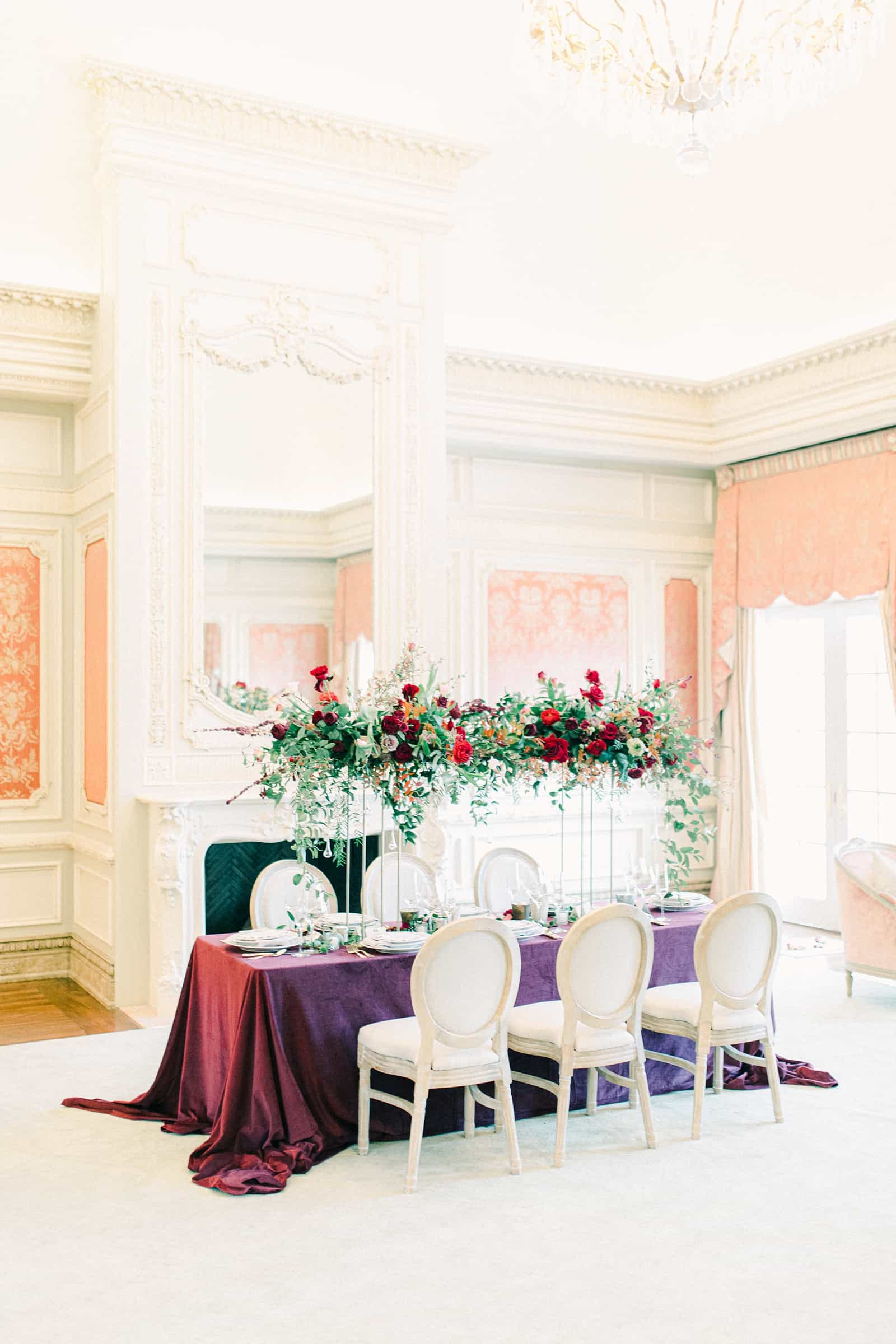 Wedding table with floral arch, maroon tablecloth in European style mansion