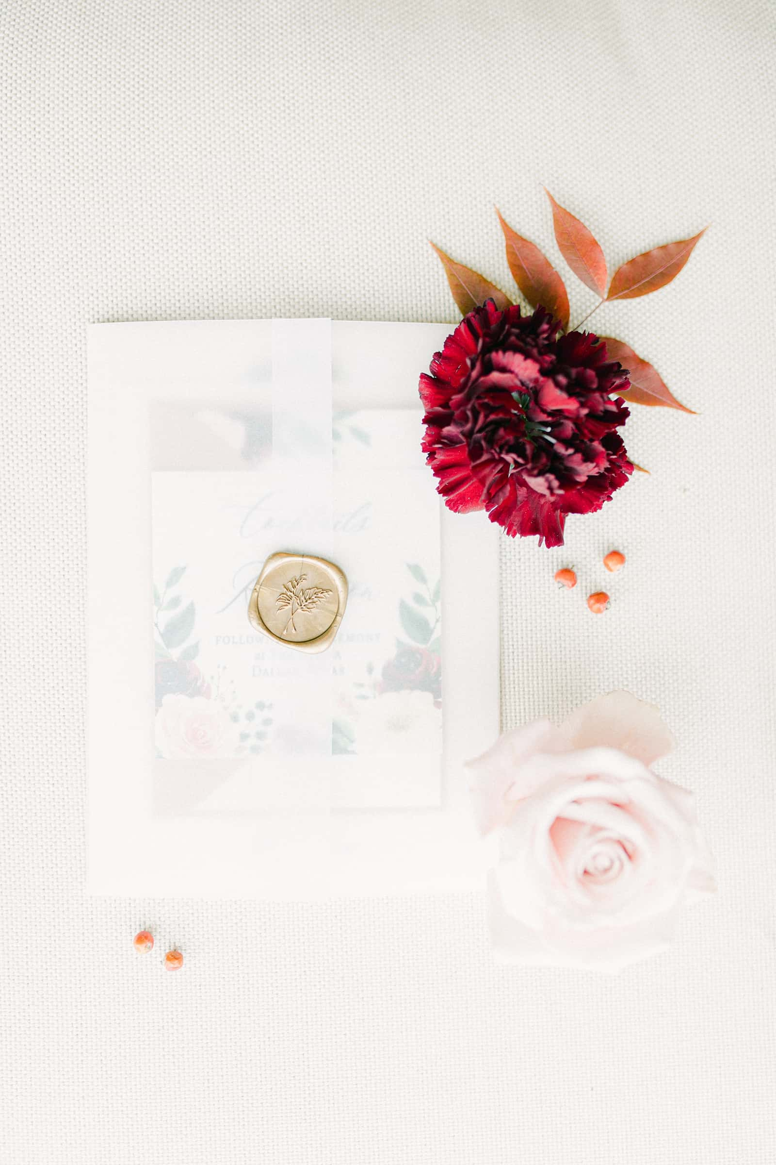 Wedding invitation with vellum paper and gold wax seal