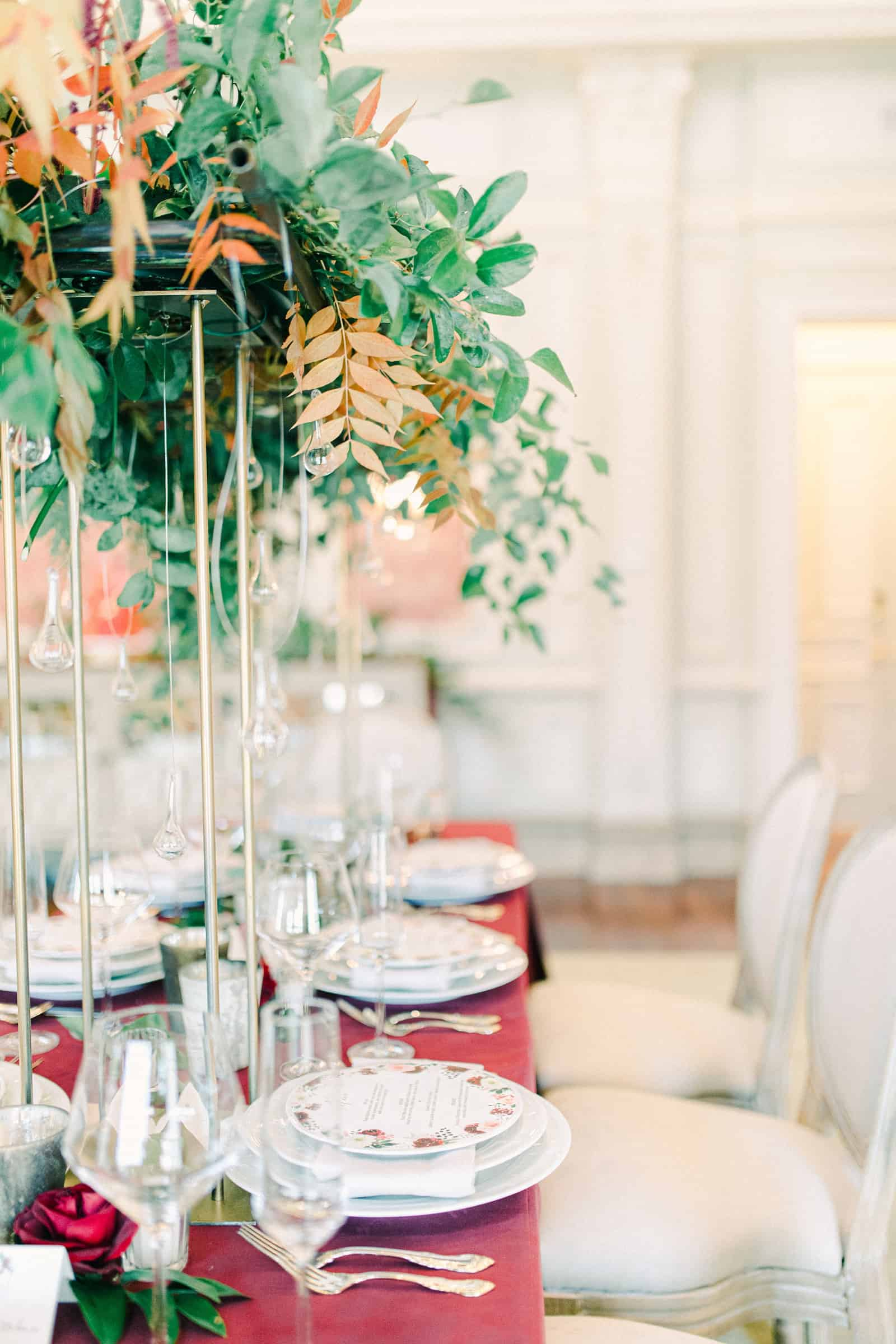 Wedding table with burgundy tablecloth and tall centerpieces