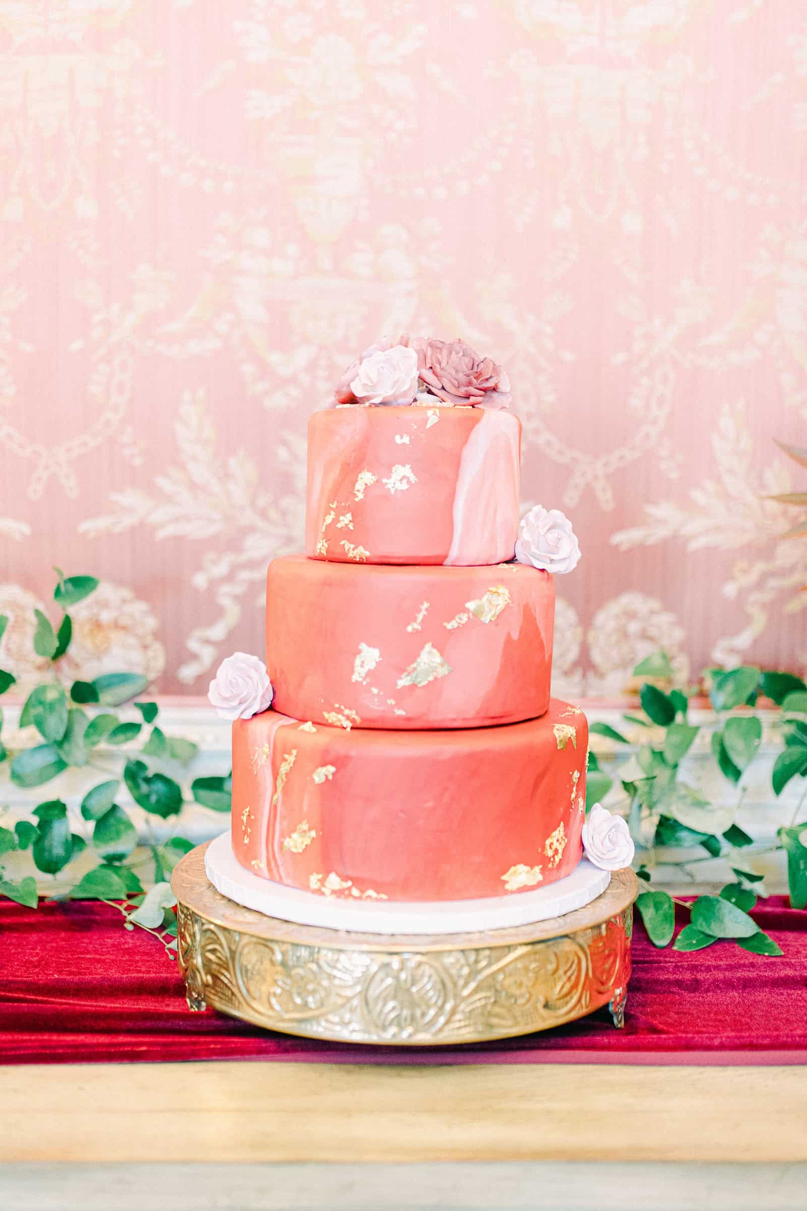 Elegant wedding cake with pink red and gold leaf