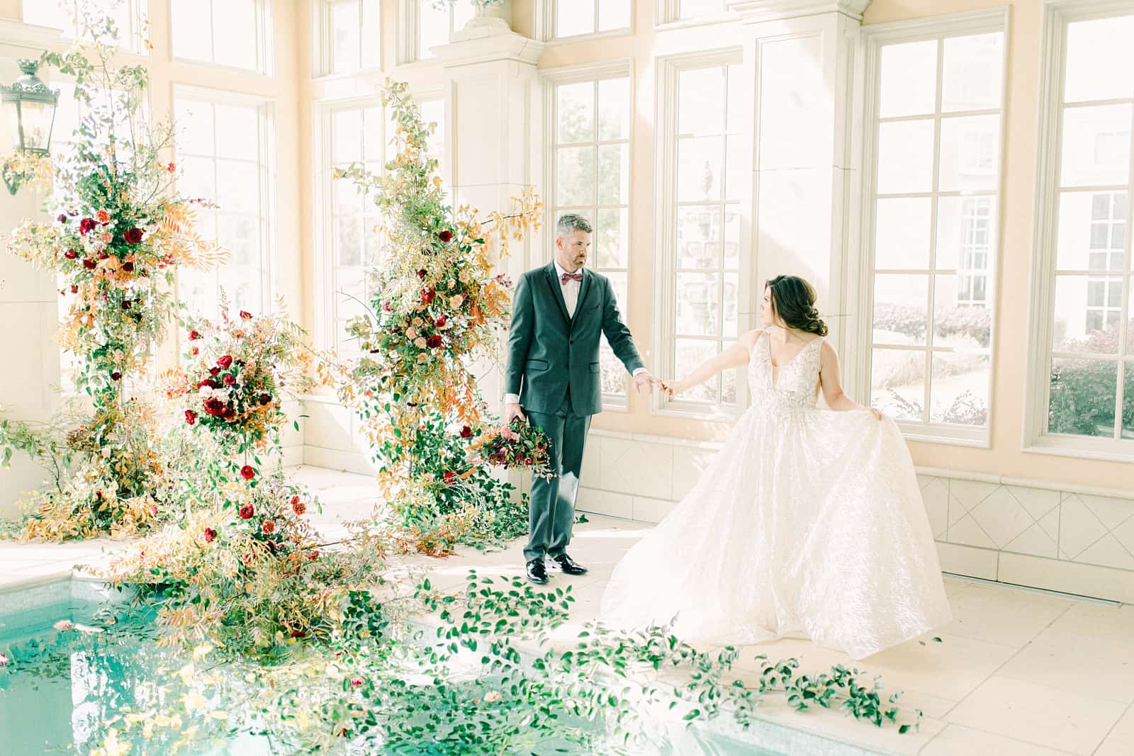 French-inspired wedding at the Olana mansion in Dallas, Texas, pool house ceremony, bride and groom dance with ceremony backdrop
