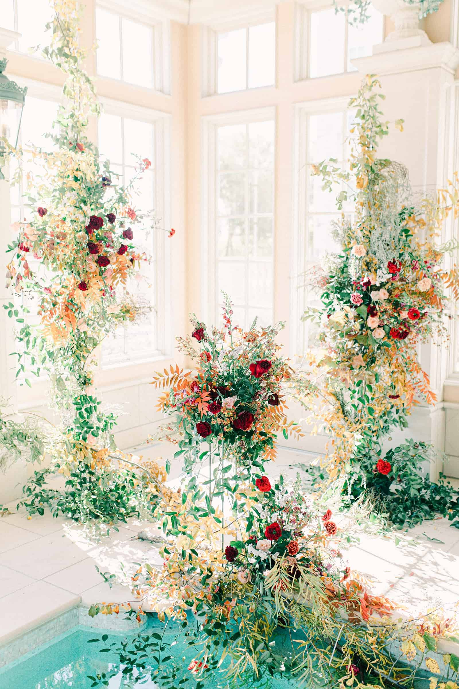 Ornate floral backdrop with lush greenery for elegant European wedding ceremony at the Olana in Dallas, Texas