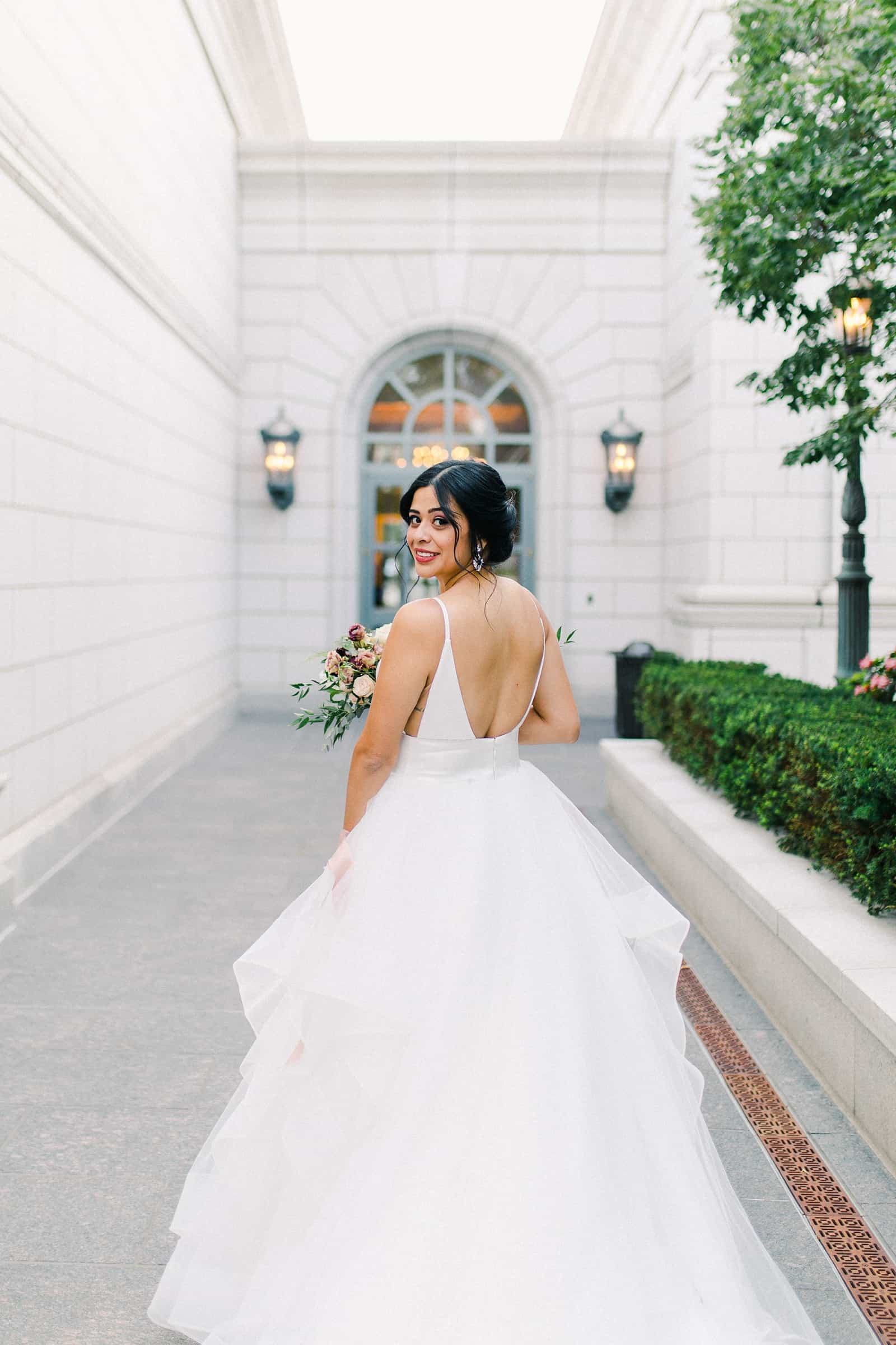 Bride with long train and low back dress in the courtyard of the Grand America Hotel in Salt Lake City, Utah
