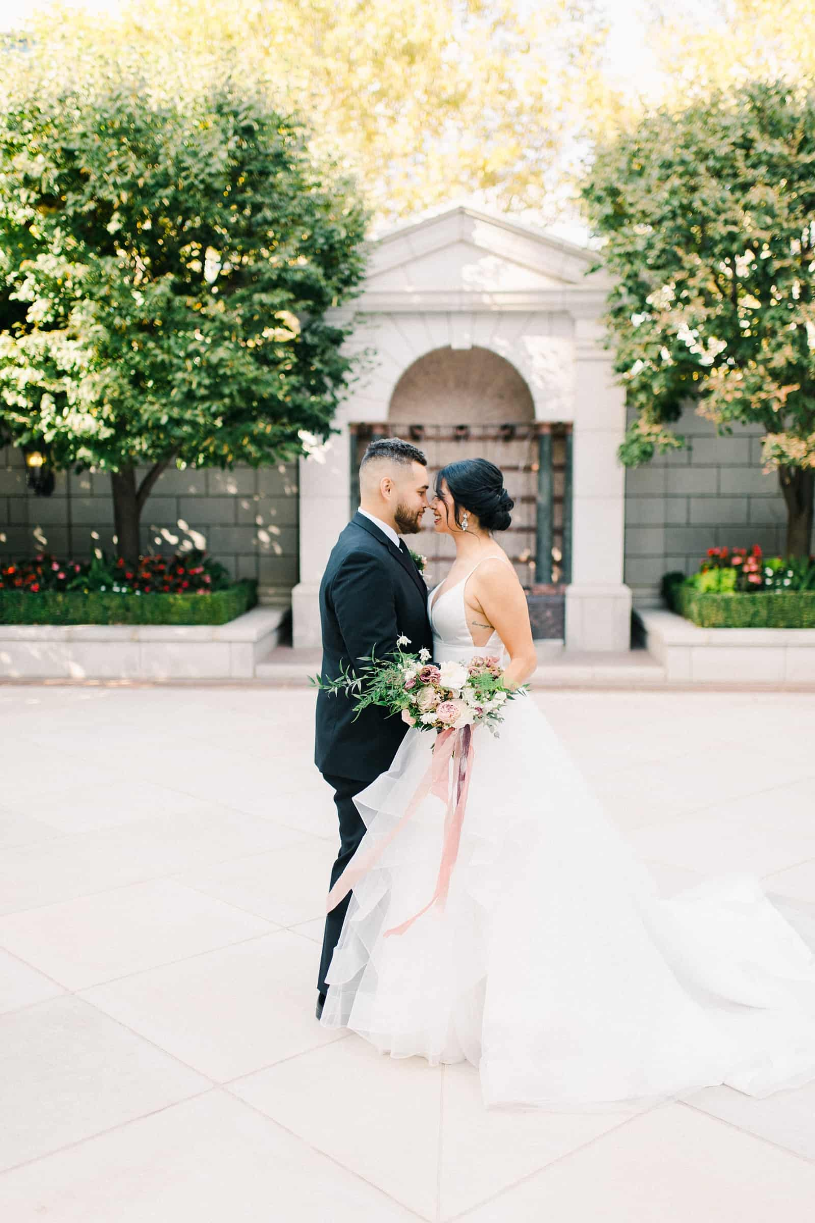 Bride and groom pose with foreheads together outside the Grand America Hotel