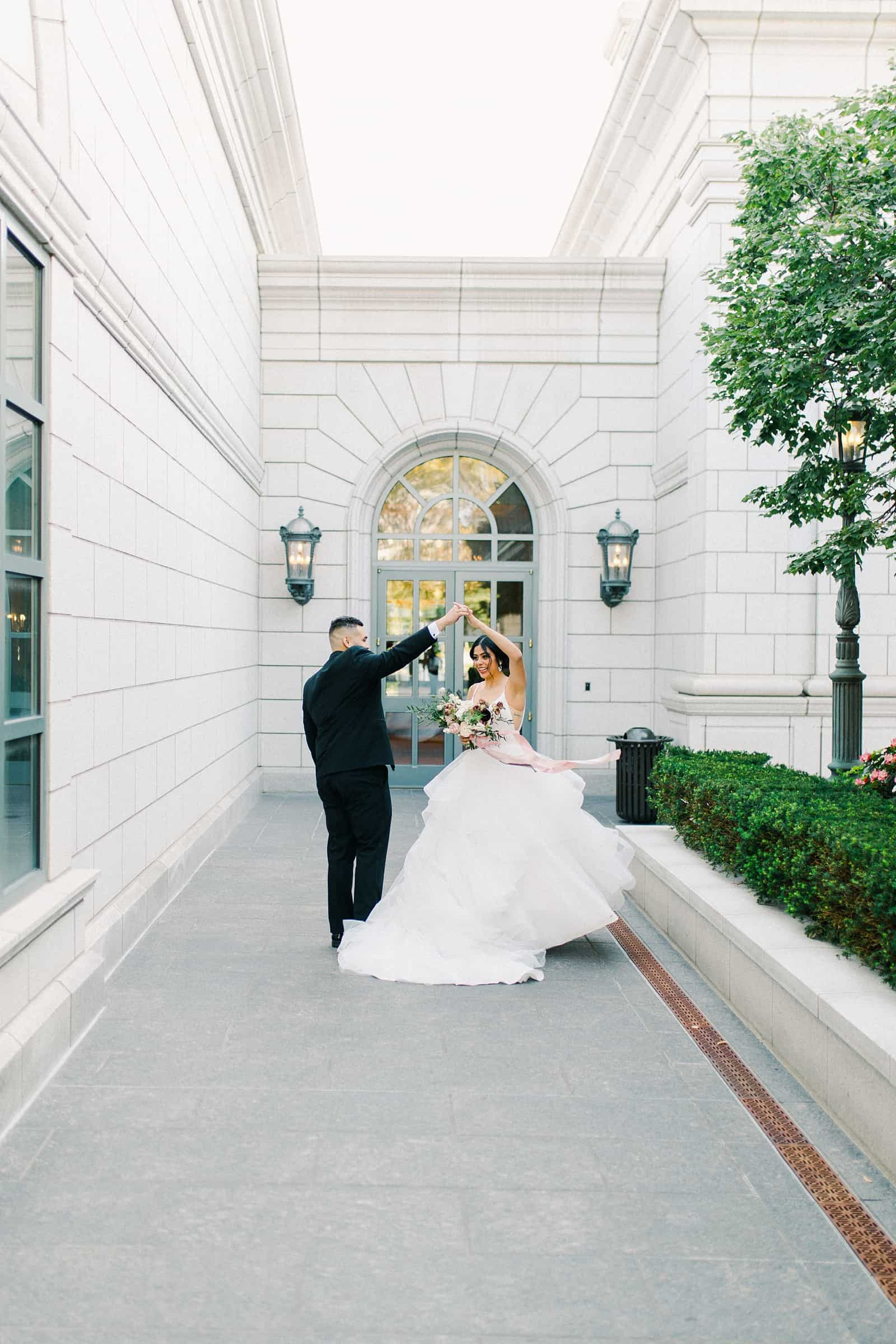 Bride and groom dancing together in the courtyard of the Grand America hotel in Salt Lake City