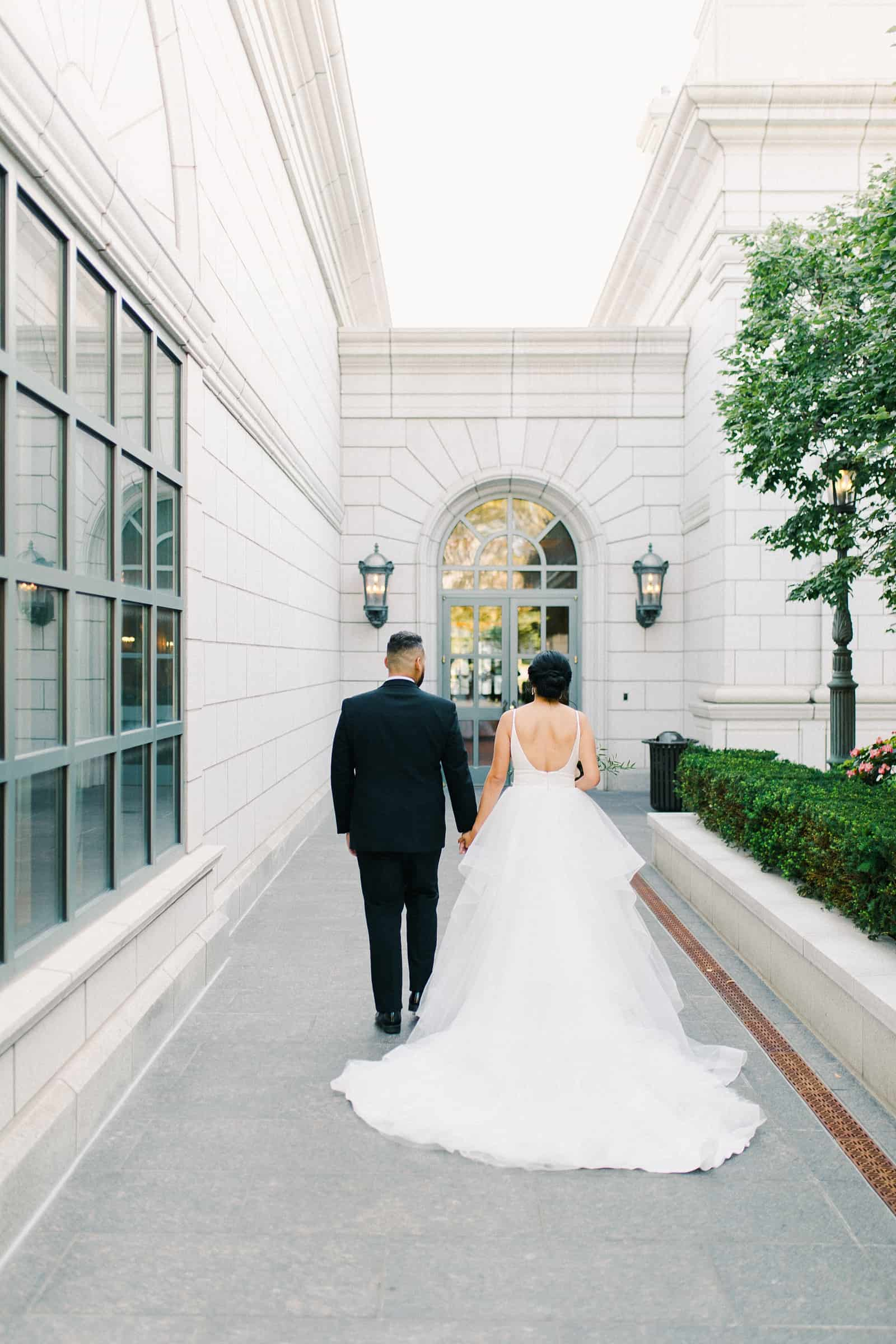 Groom and bride with long train walk together