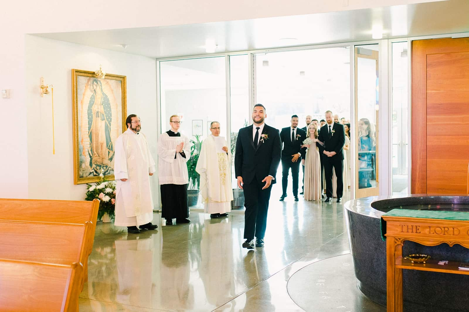 Groom walks down the aisle in traditional Catholic ceremony