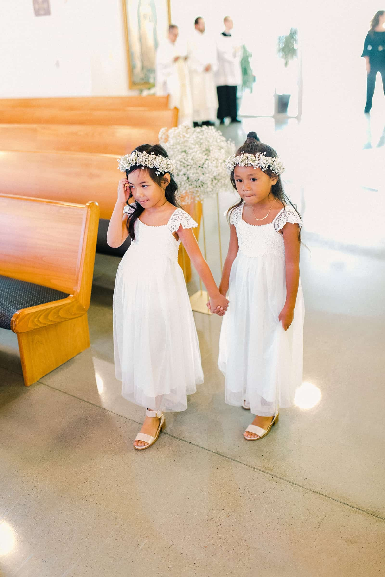 Flower girls with baby's breath flower crowns and white dresses walk down the aisle