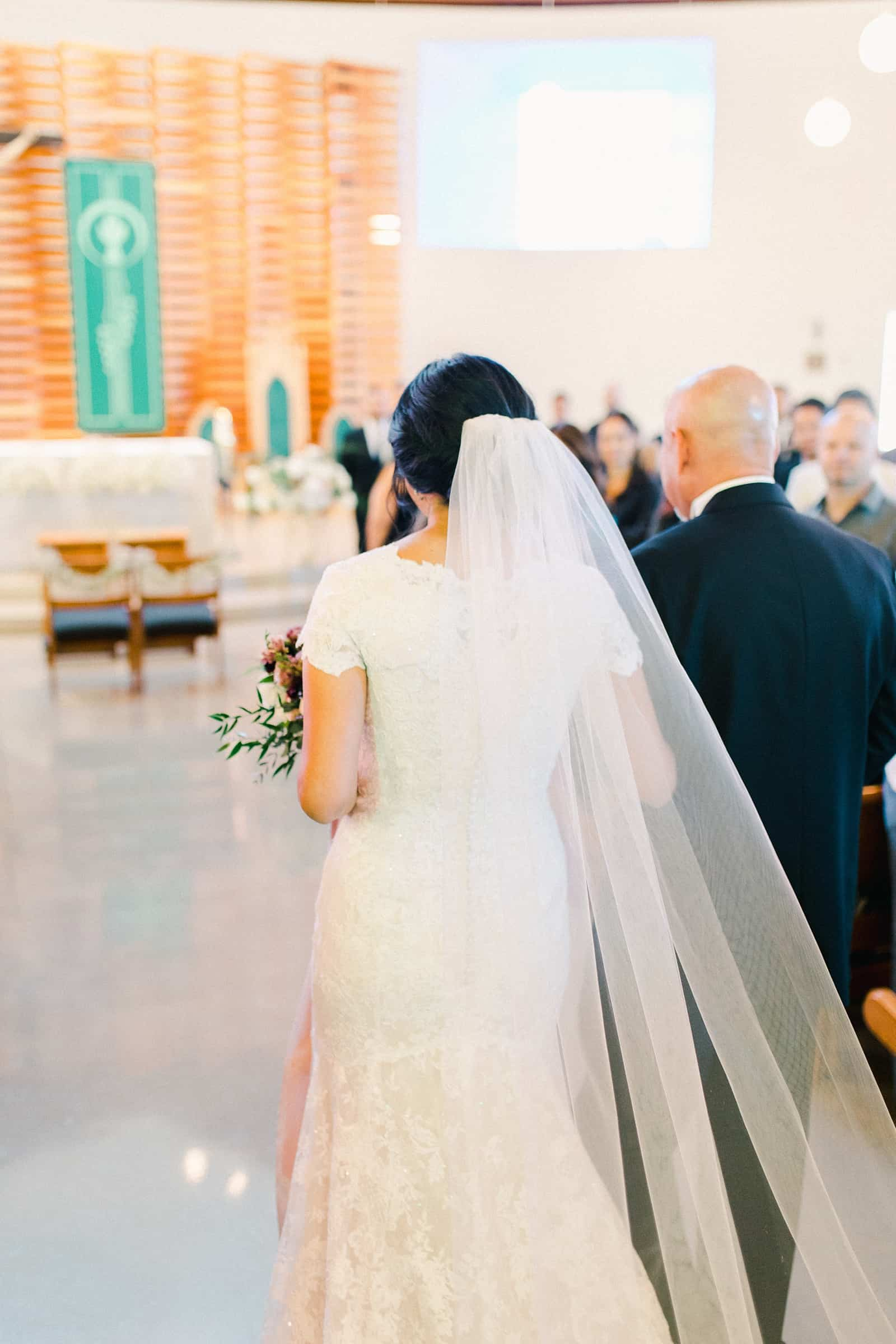 father of the bride walks her down the aisle with long veil and train