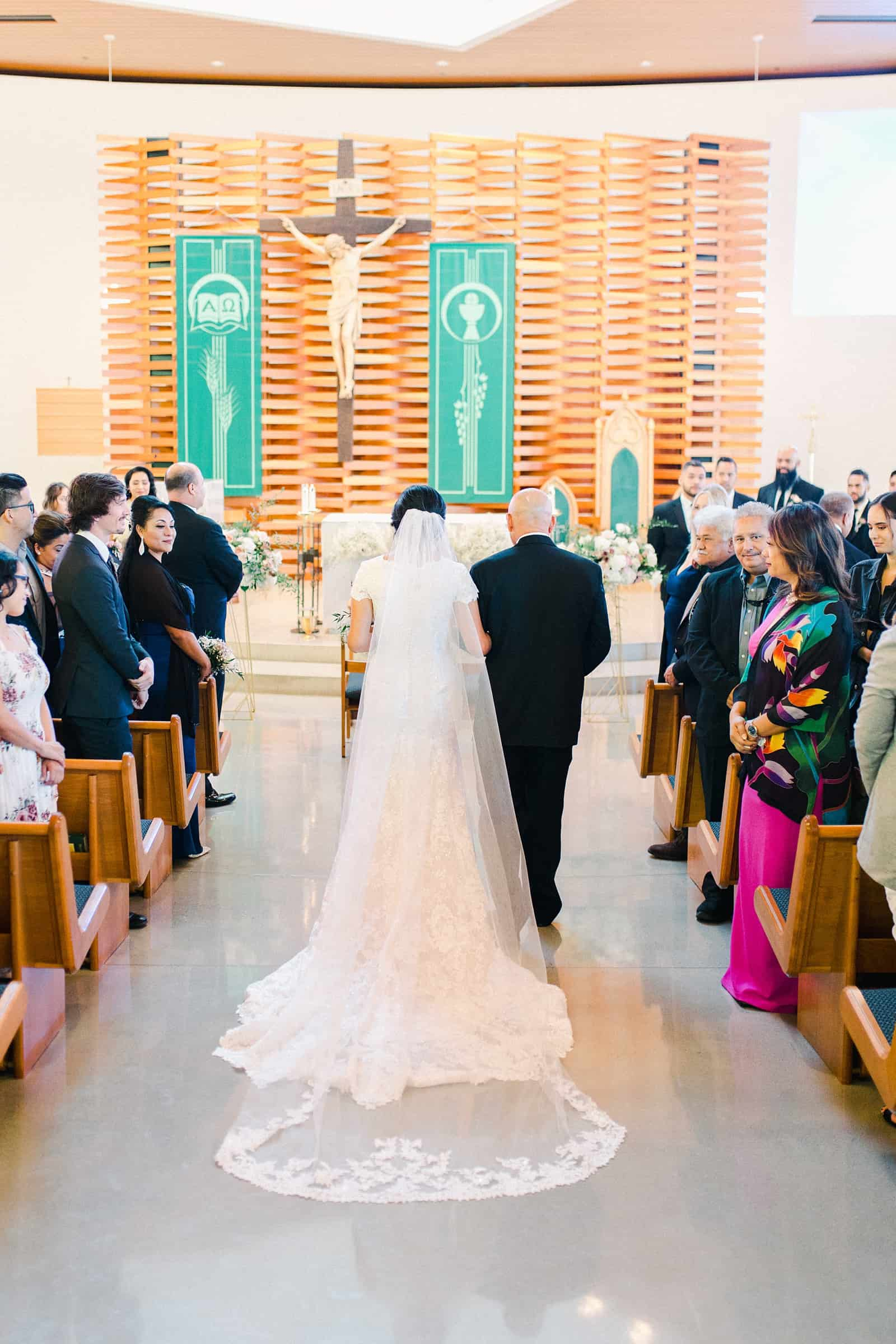 father of the bride walks her down the aisle in traditional Catholic ceremony