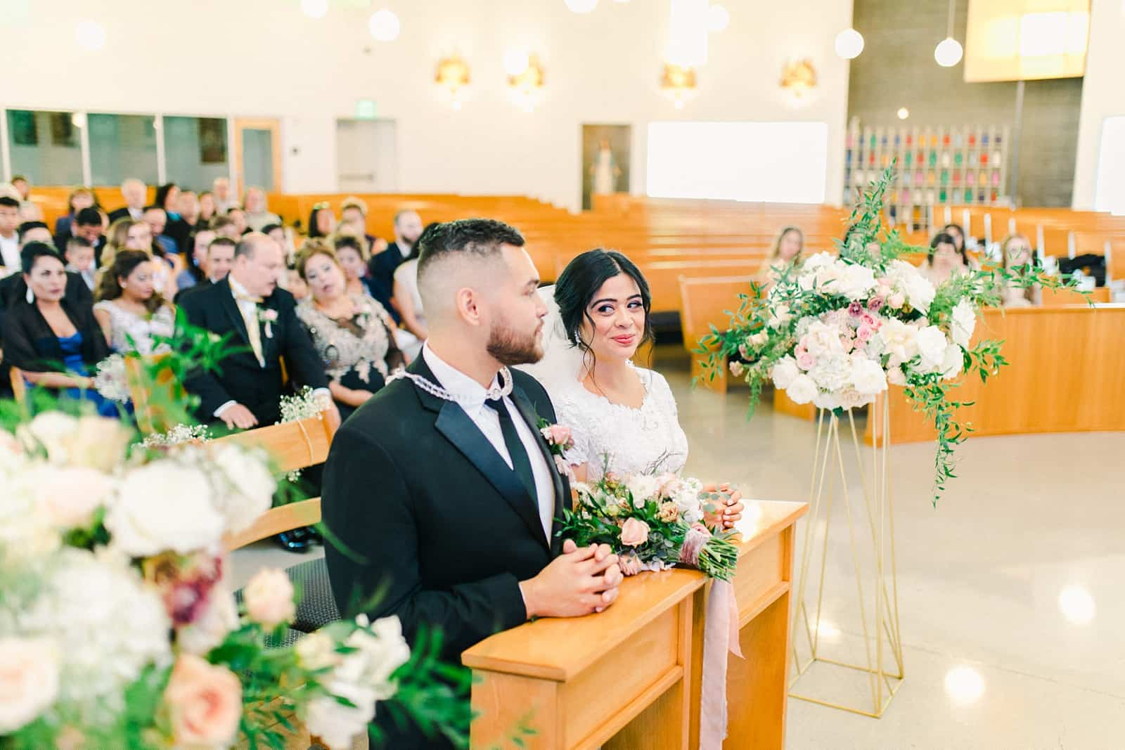 Bride and groom kneel during traditional catholic mass ceremony