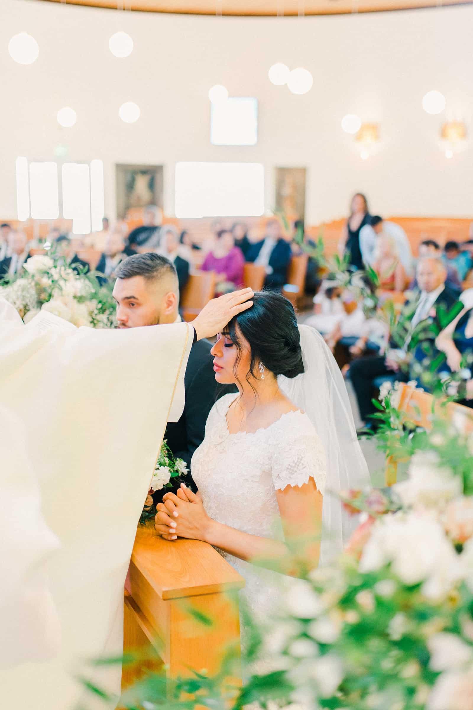 Bride with priest pray during catholic wedding ceremony