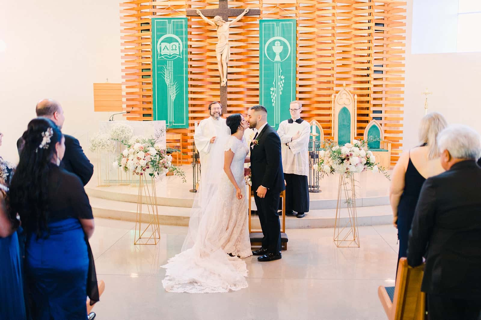 Bride and groom kiss during traditional Catholic ceremony