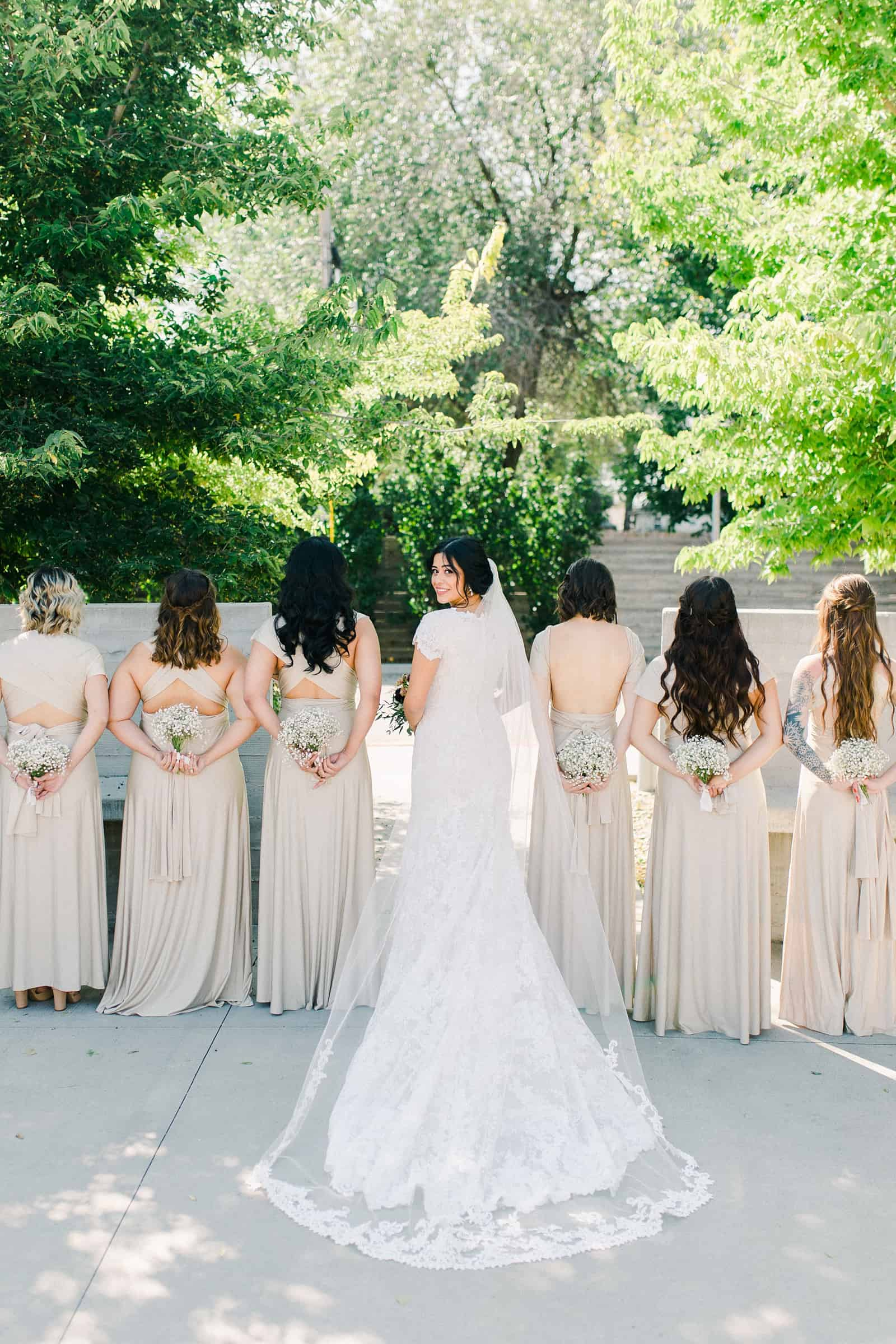 bride with long train and bridesmaids wearing gold champagne long maxi bridesmaids dresses with baby's breath bouquets,