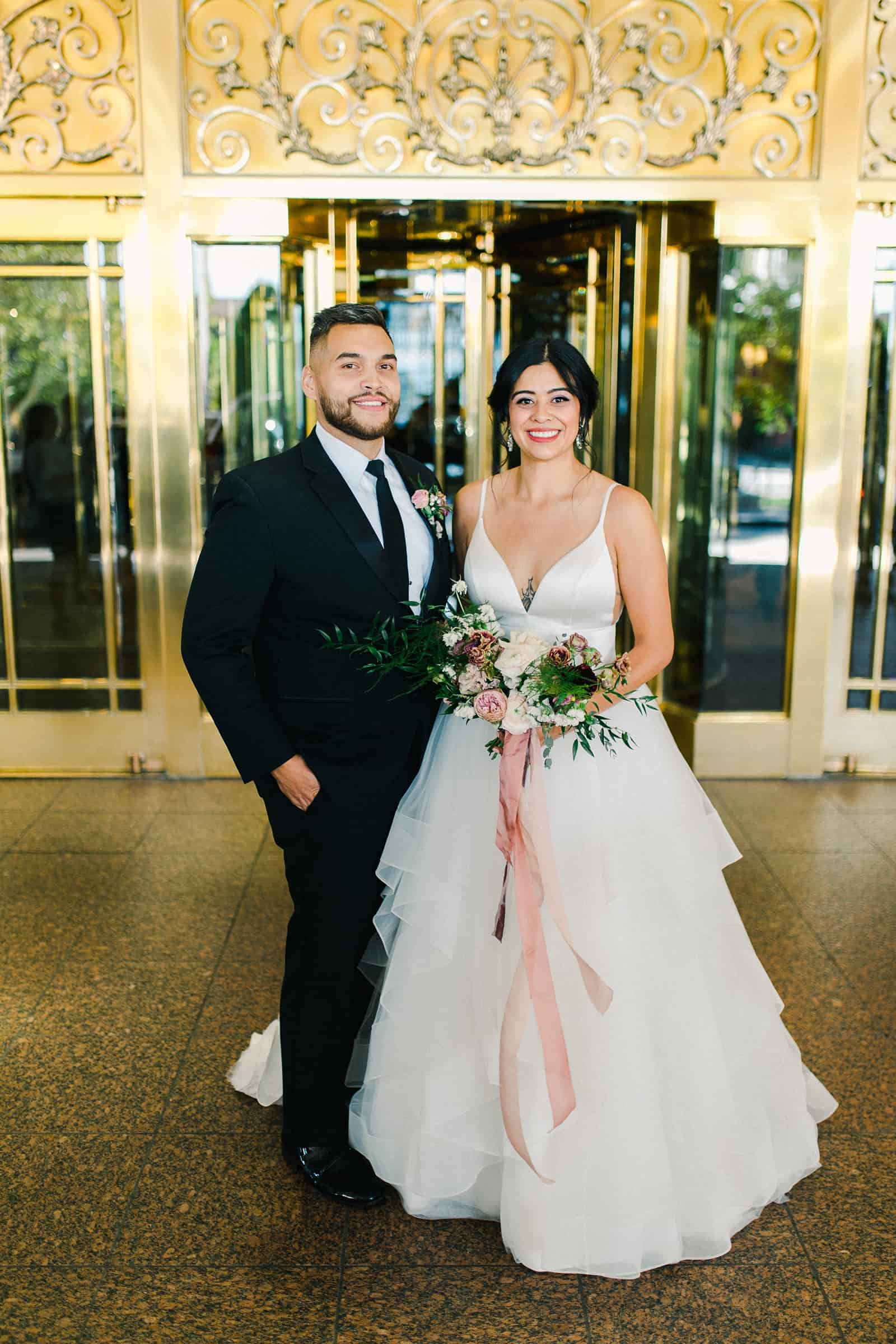 Bride and groom smile in front of gold doors