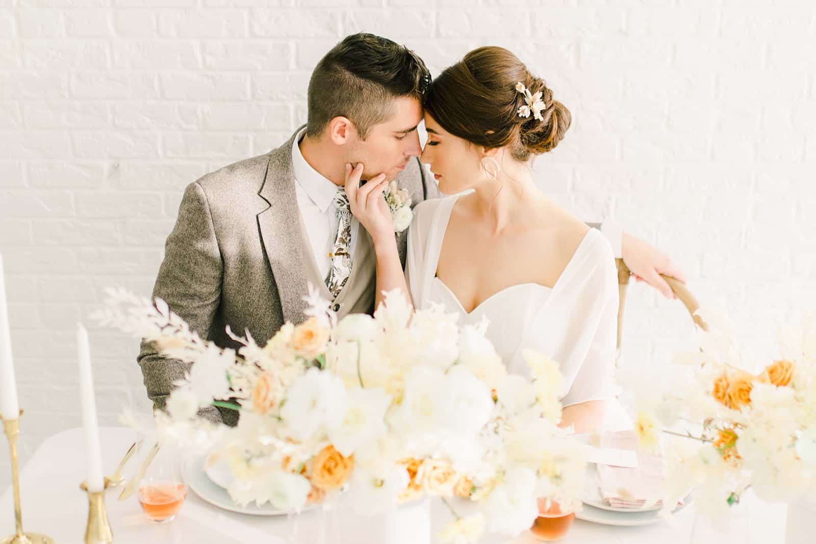 Bride and groom lean close sitting at modern wedding table with white and orange flowers