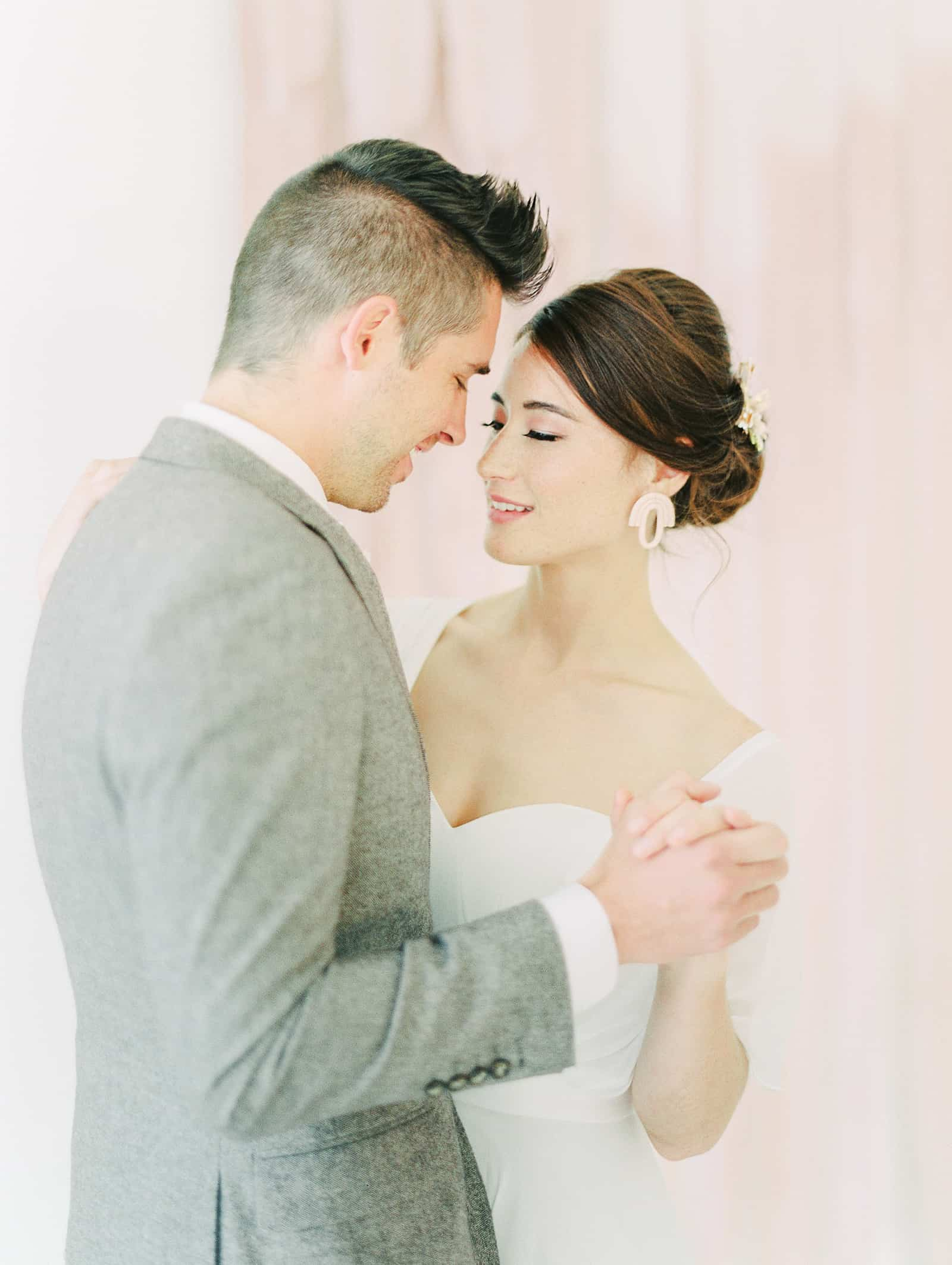 Modern bride and groom dance in front of blush pink watercolor backdrop