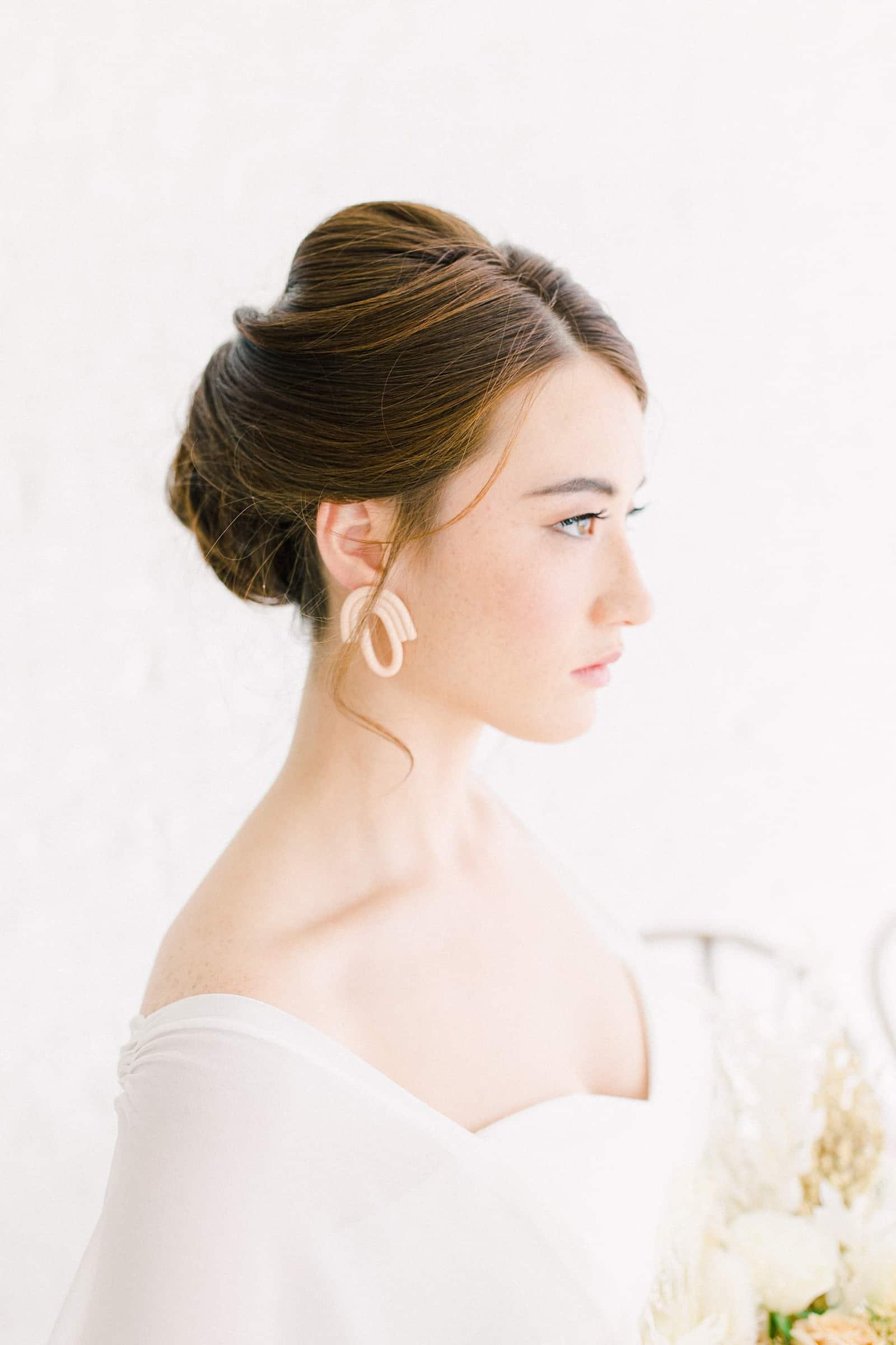 Modern bride with sleep updo, statement earrings and sweetheart neckline