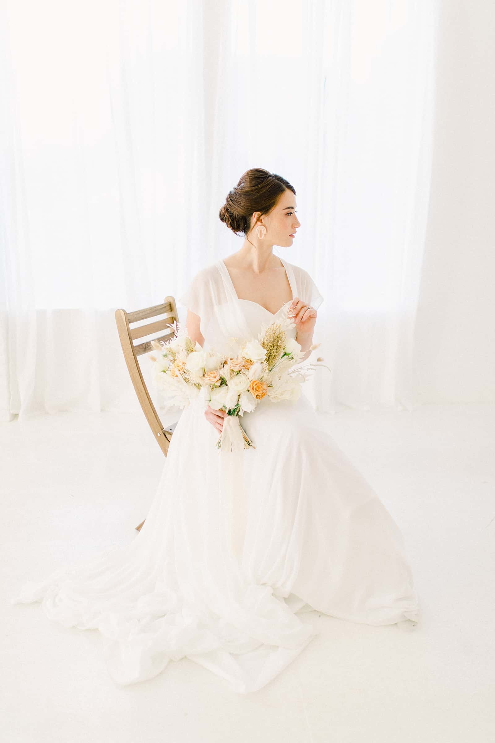 Modern bride sitting with simple, neutral bouquet and sweetheart neckline
