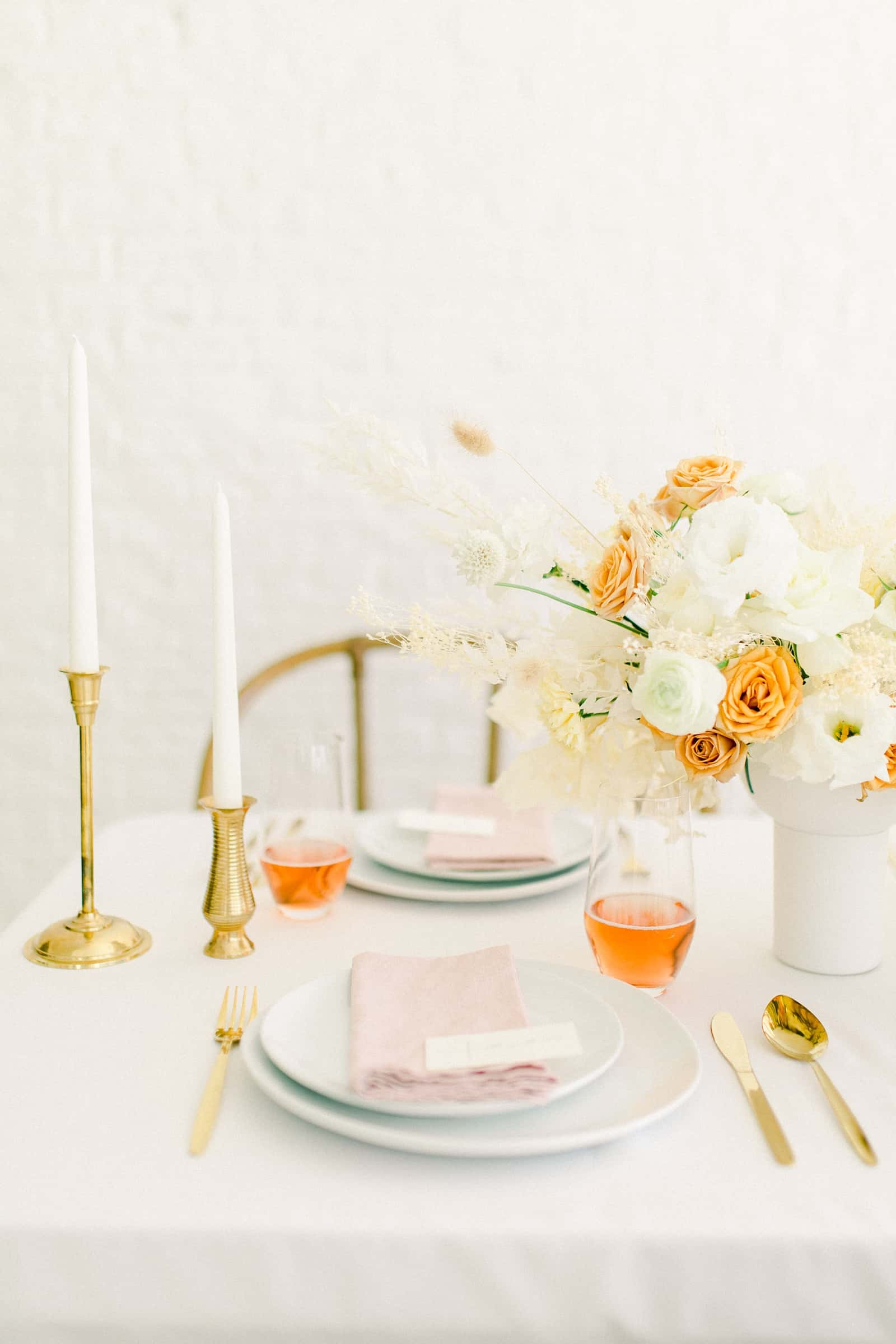 Modern wedding table scape with white and orange flower centerpiece and blush pink napkins