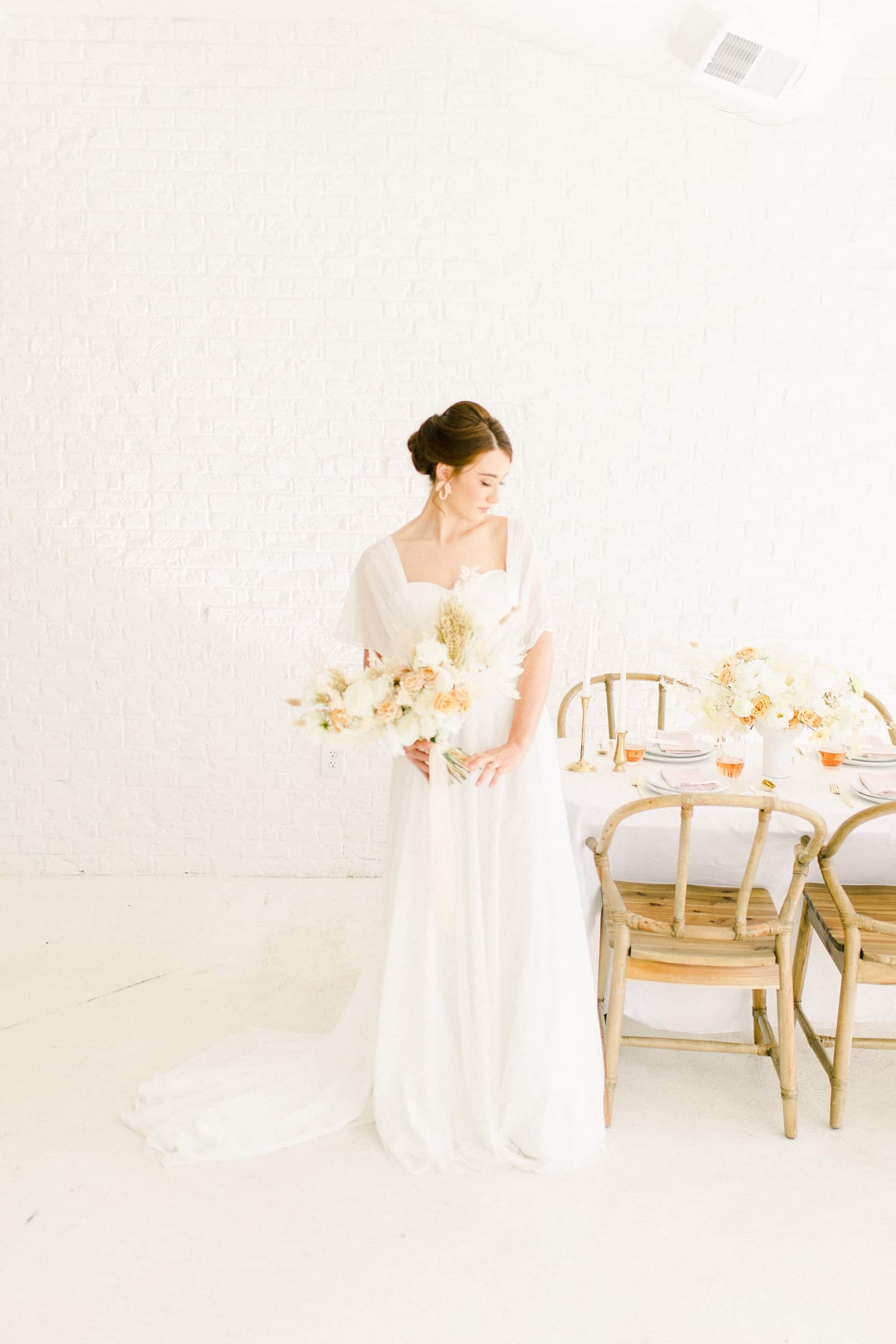 Bride standing next to Modern wedding table settings with white tablecloth and neutral colors