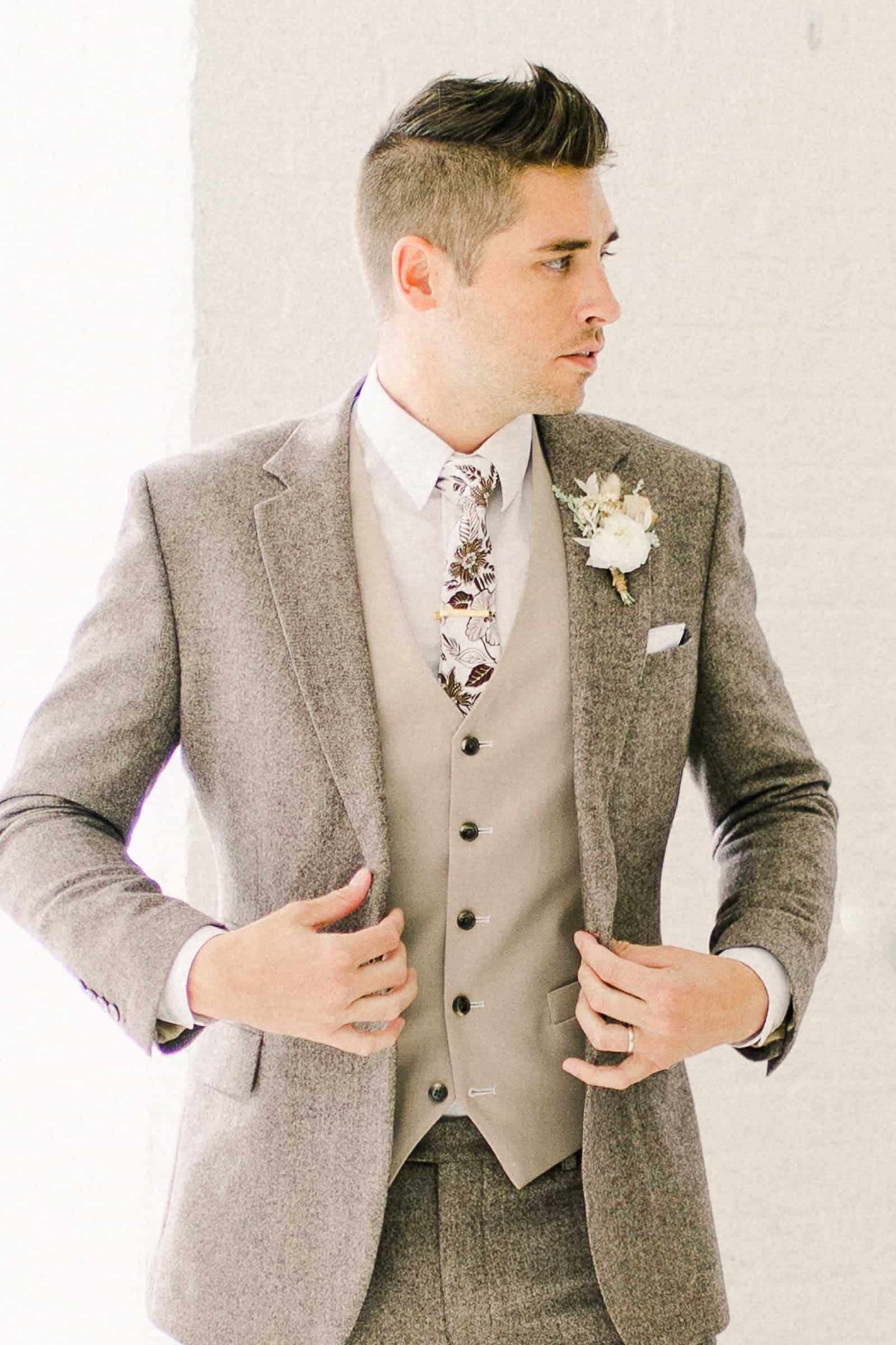 Modern groom wearing oatmeal gray custom three piece suit with fall floral tie and a vest