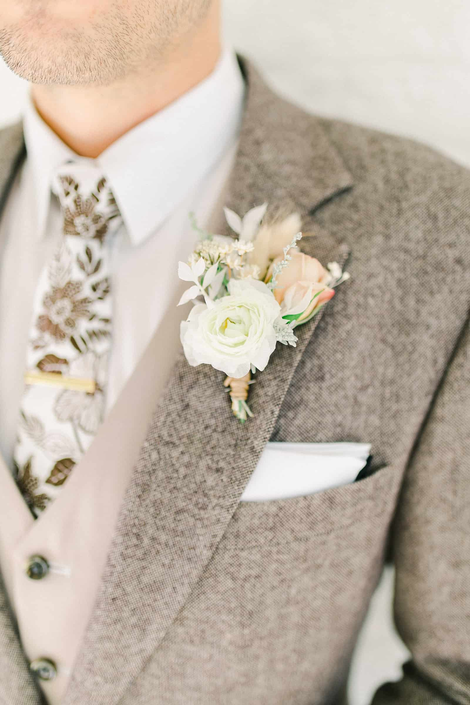 Modern groom wearing oatmeal gray custom three piece suit with fall floral tie and a vest, white neutral boutonniere