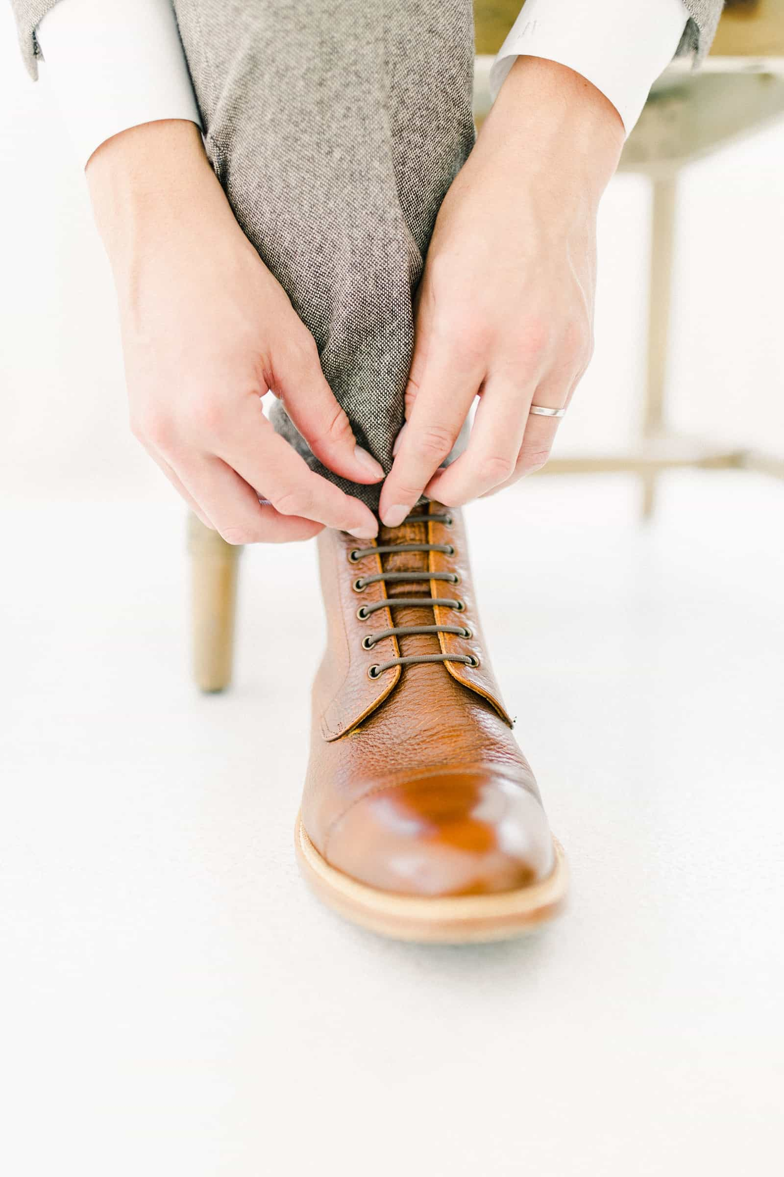 Modern groom putting on brown leather shoes