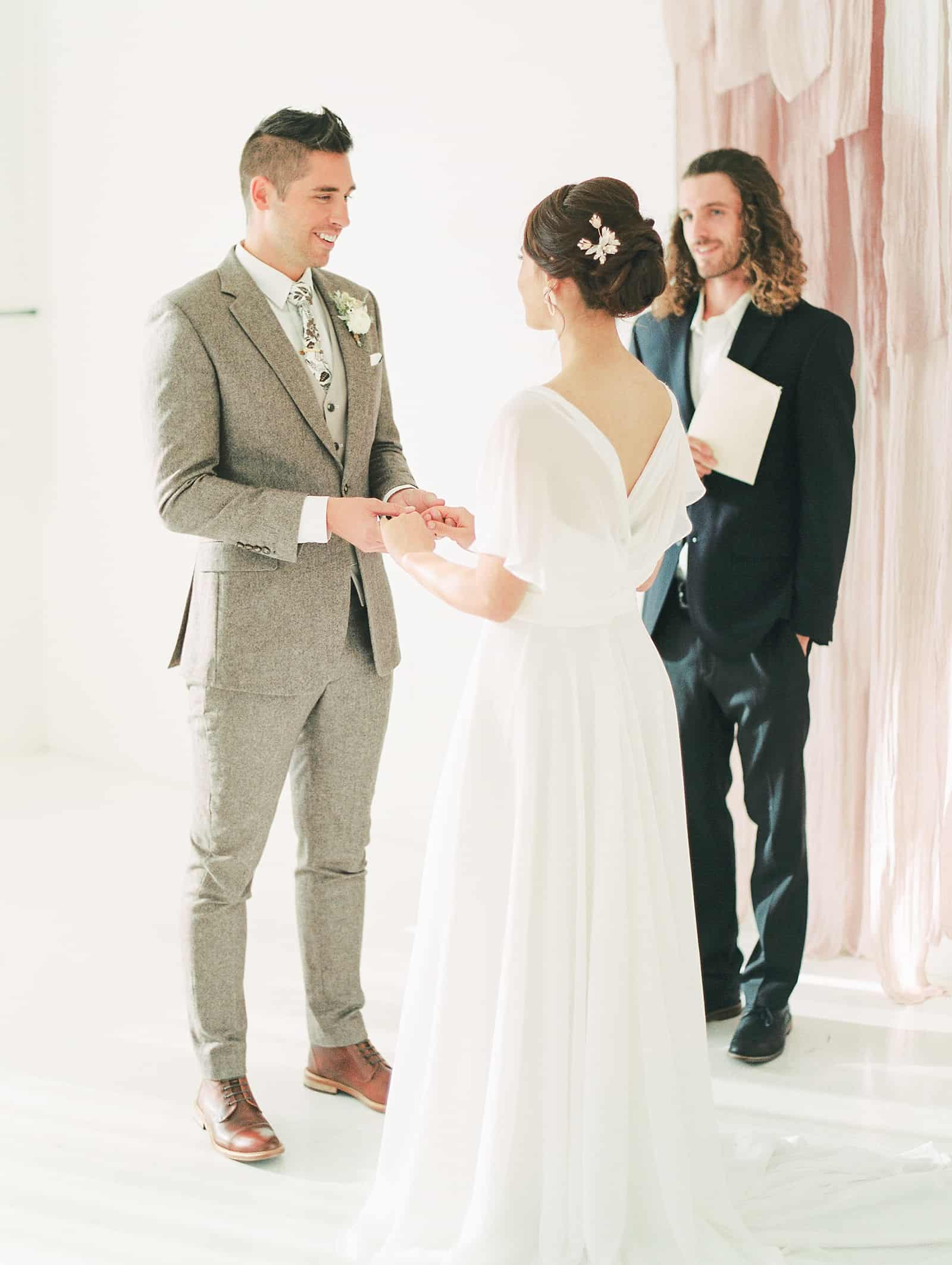 Groom in beige gray suit says his vows and smiles