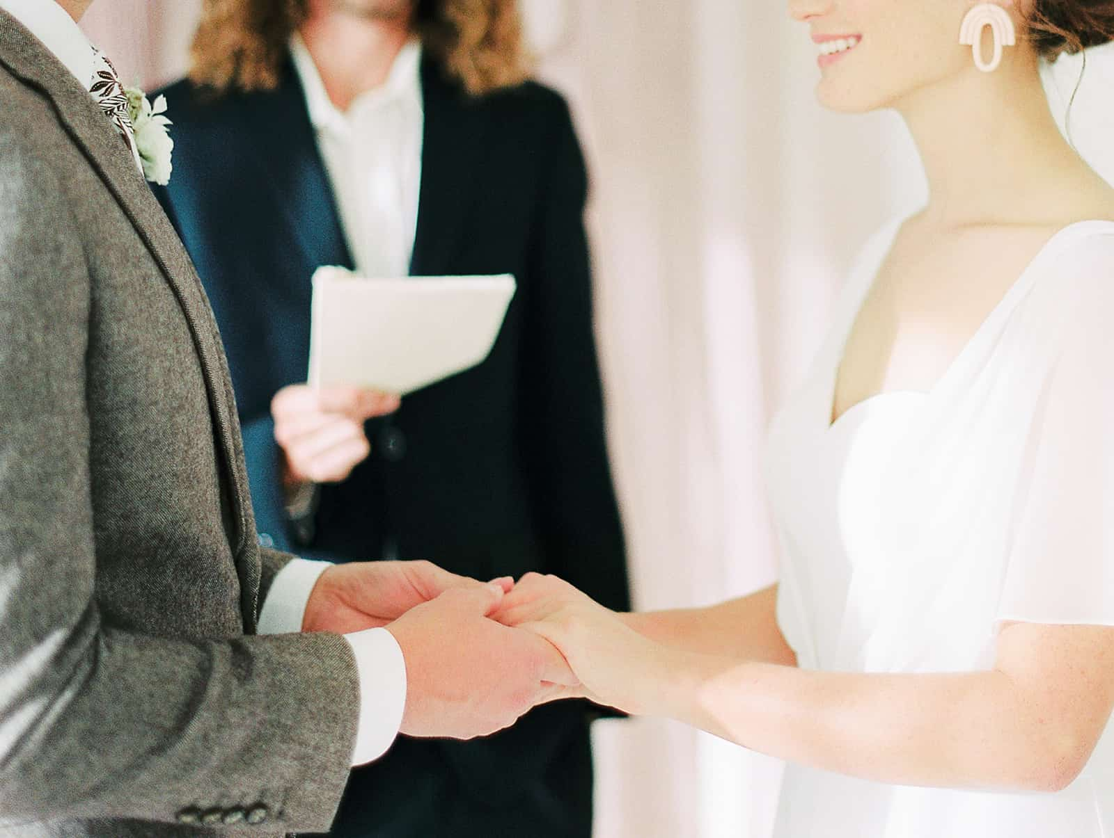 Bride and groom hold hands during small wedding ceremony