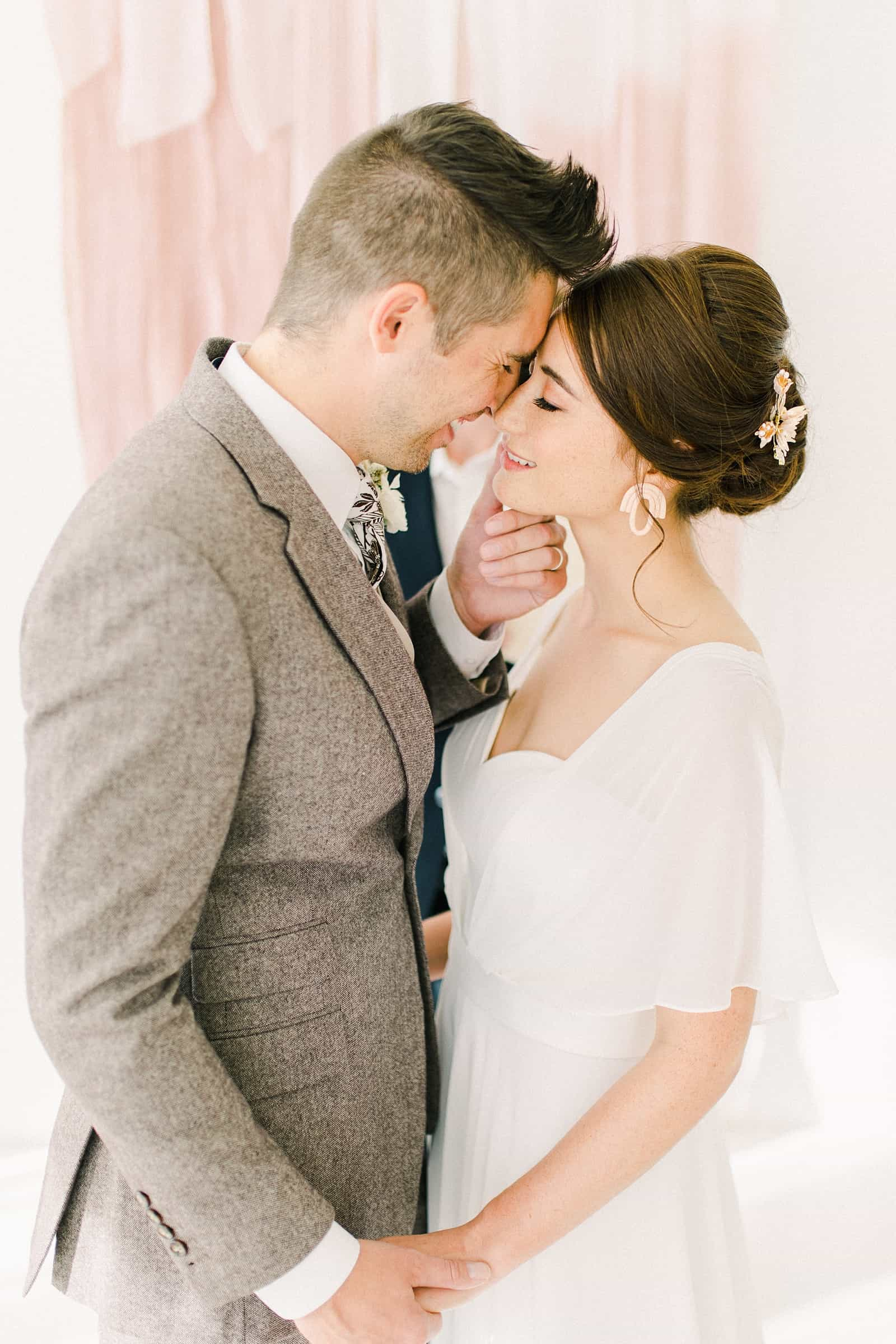 Bride and groom first kiss in front of blush pink painted ombre watercolor backdrop