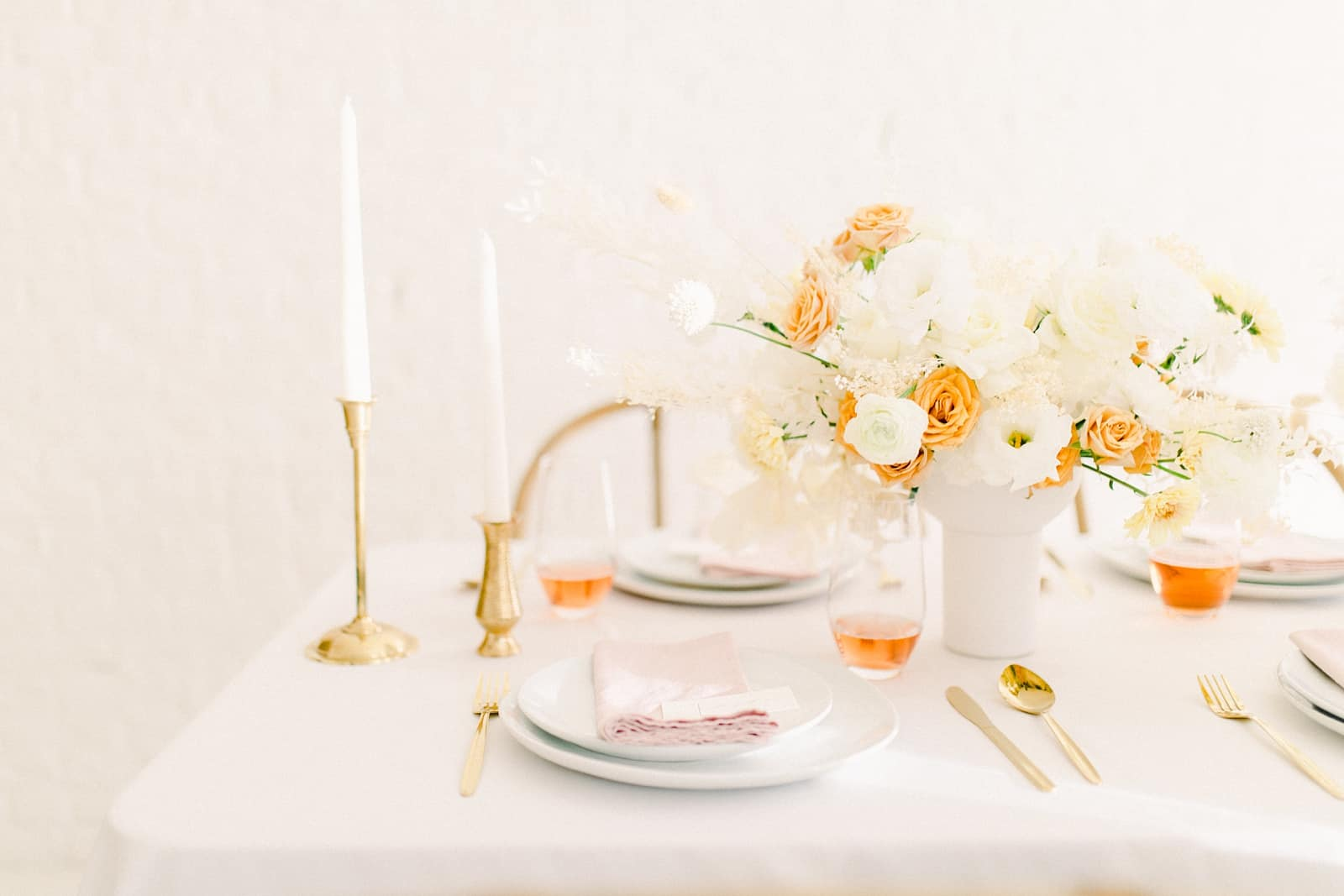 Modern wedding table scape with white and orange flower centerpiece and blush pink napkins and gold candlesticks
