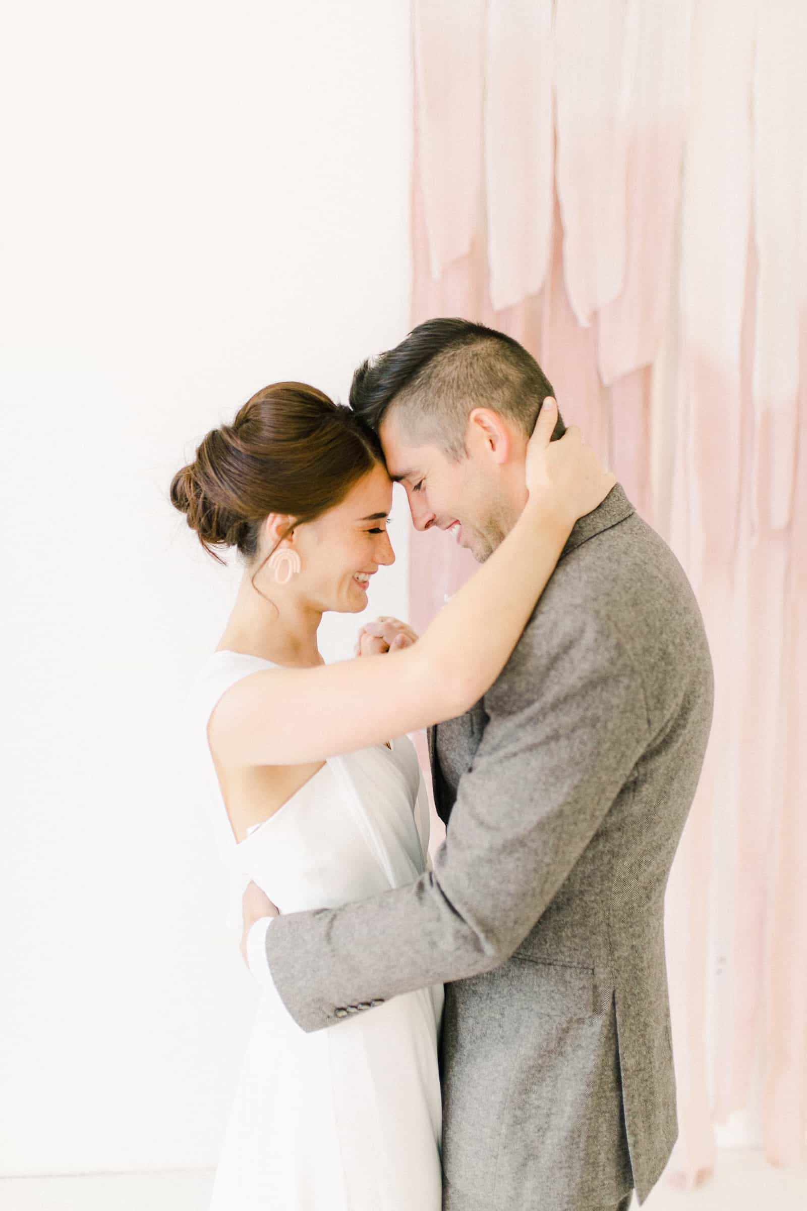 Bride and groom in front of blush pink painted ombre watercolor backdrop