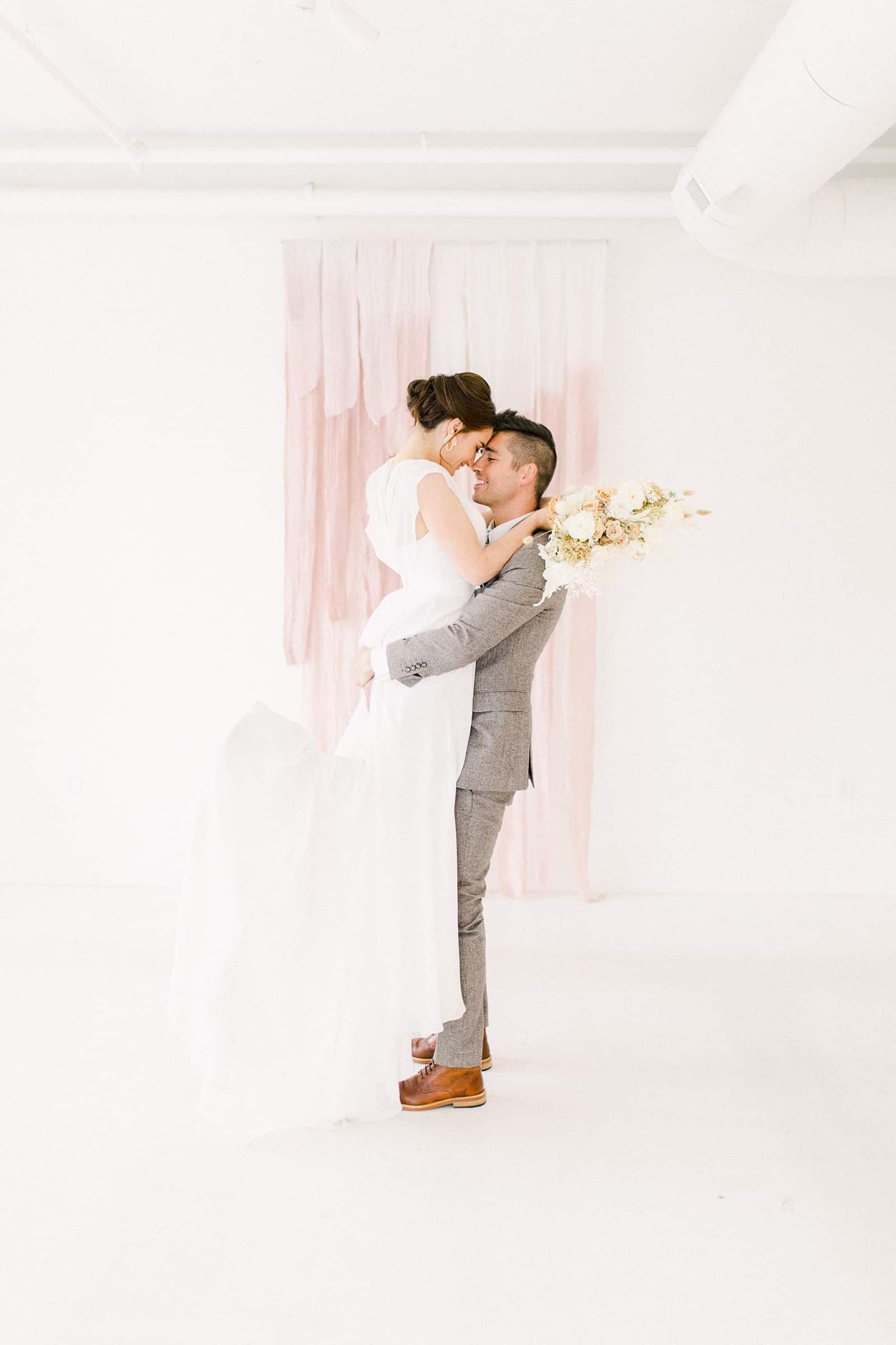 Groom lifts bride after ceremony in front of blush pink painted ombre watercolor backdrop
