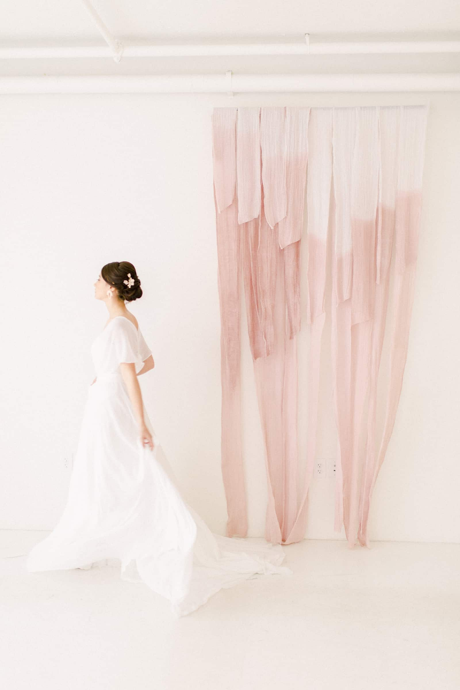 Modern bride walks in front of blush pink painted cheesecloth ombre watercolor backdrop