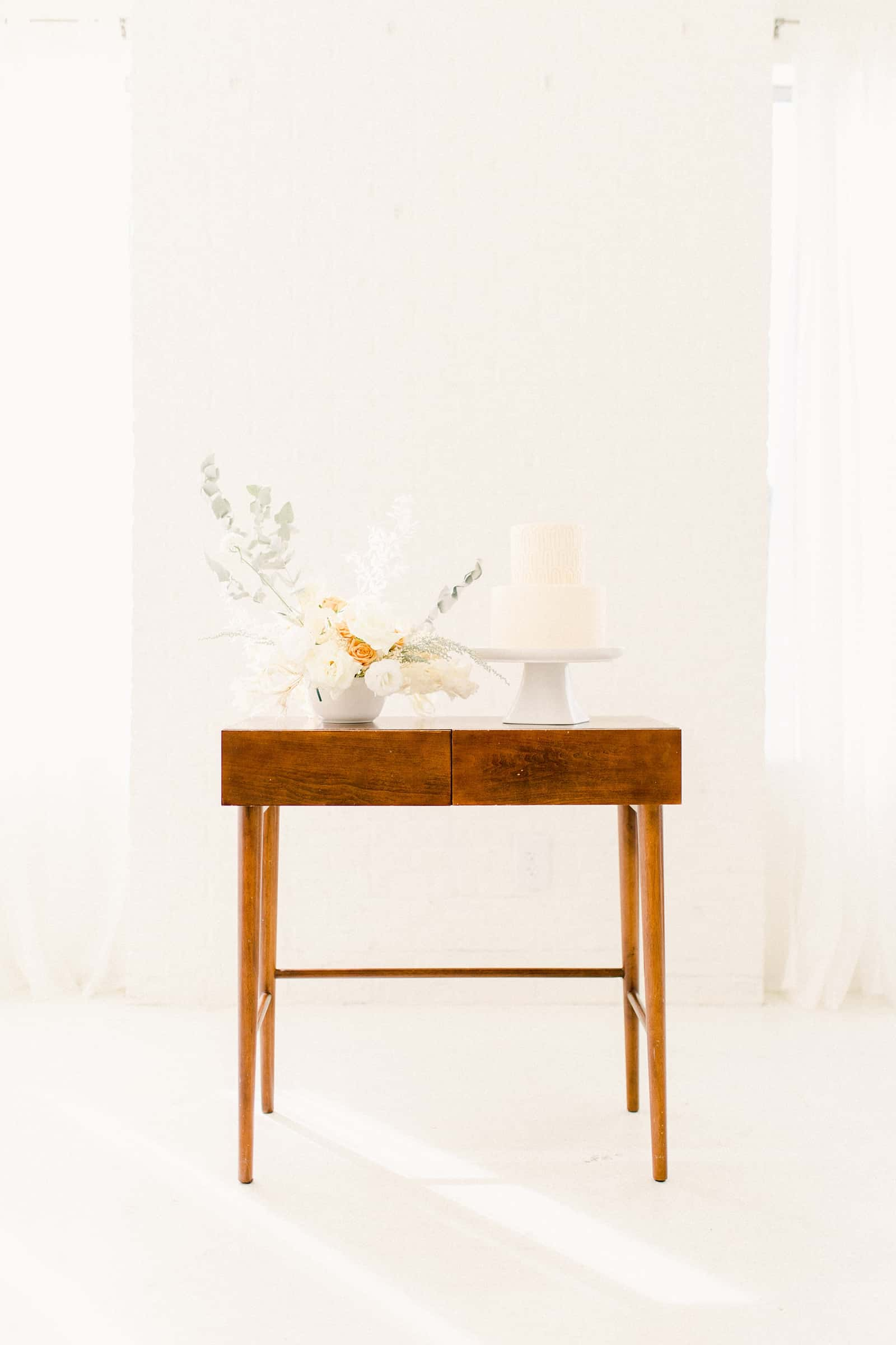 Modern wooden wedding cake table with minimalist neutral flowers