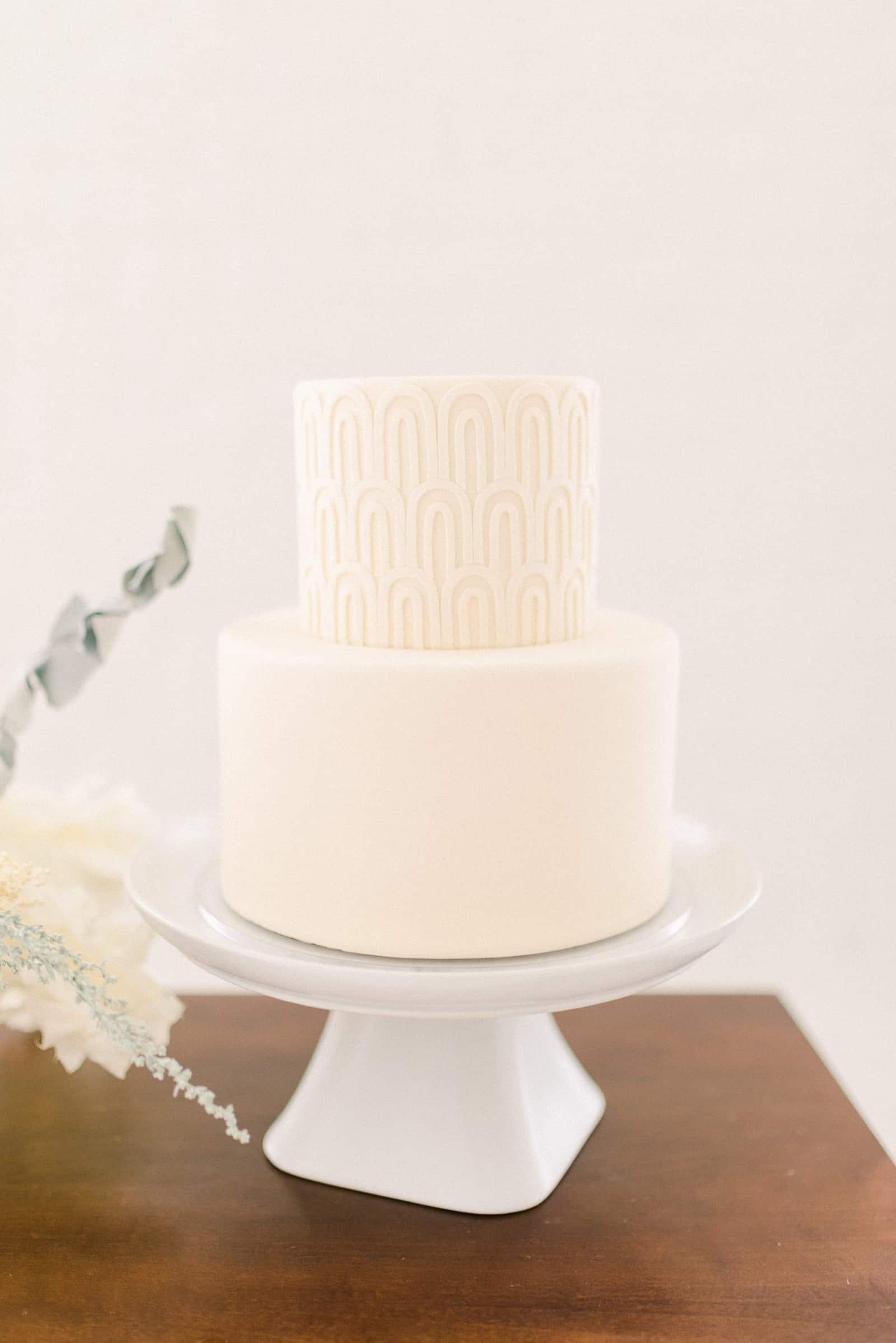 Modern minimalist white wedding cake with geometric design