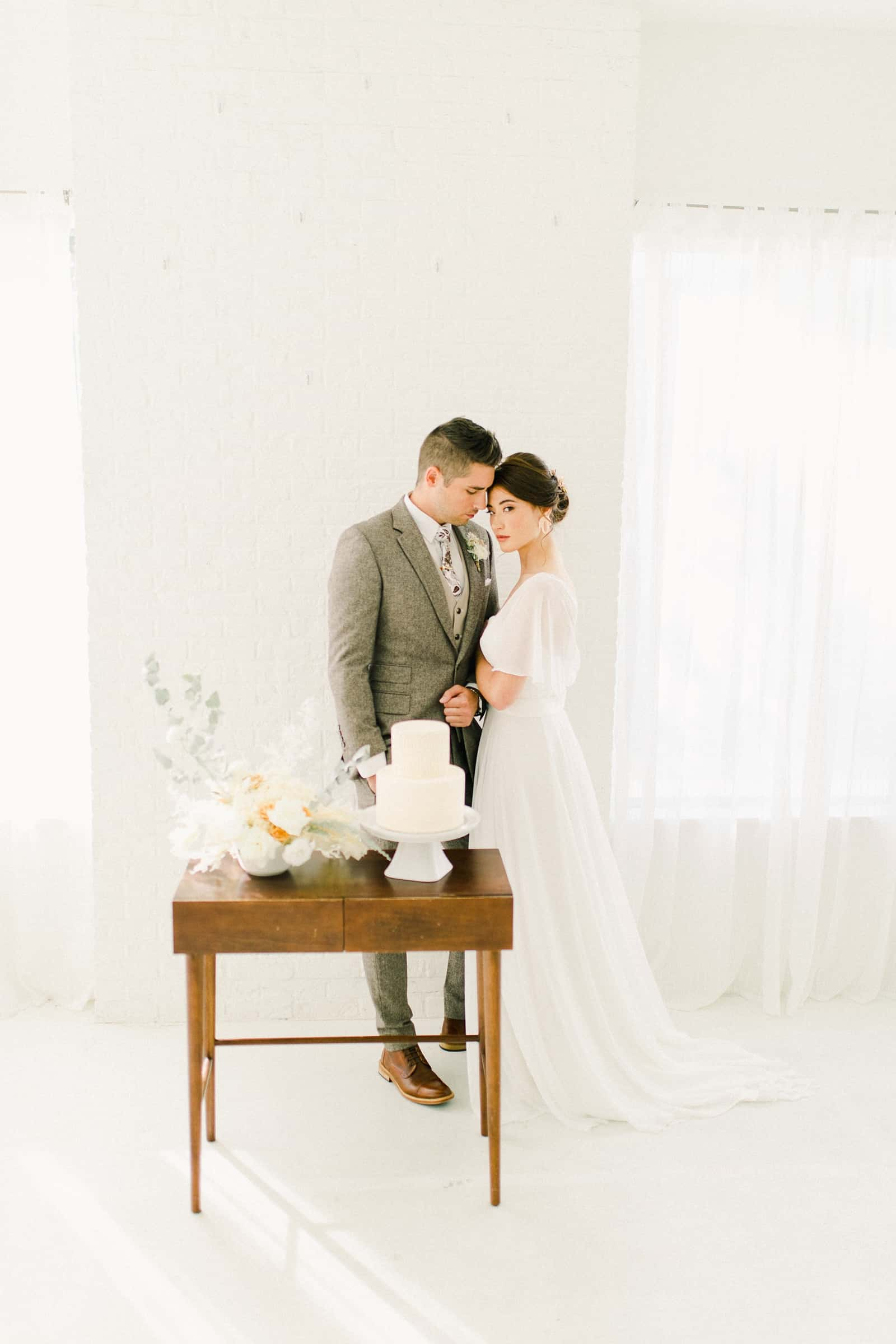Bride and groom stand in front if Modern wooden wedding cake table with minimalist neutral flowers
