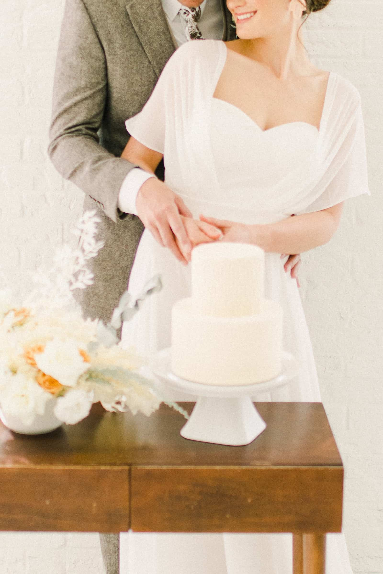 Bride and groom cut the cake, Modern minimalist white wedding cake with geometric design