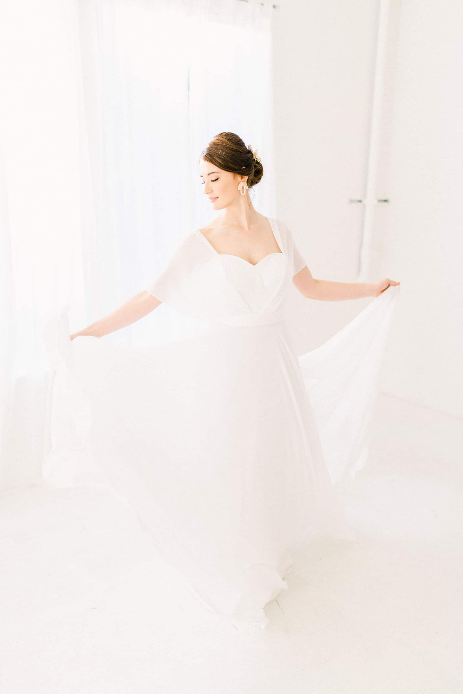Bride wearing simple modern chiffon flowy wedding dress with sweetheart neckline
