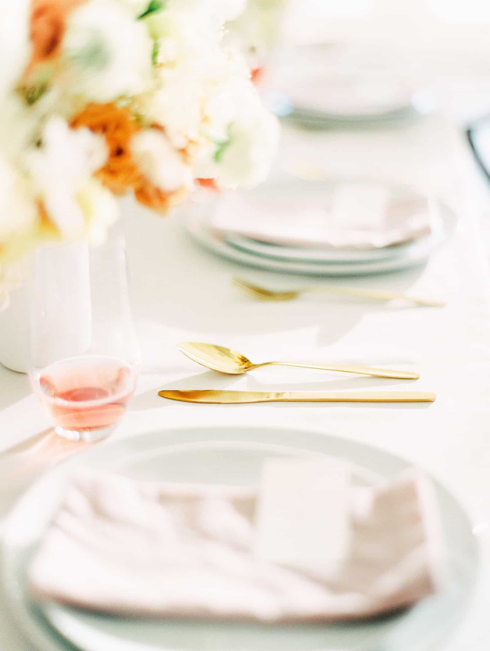 Modern wedding table scape with white and orange flower centerpiece and blush pink napkins and gold cutlery