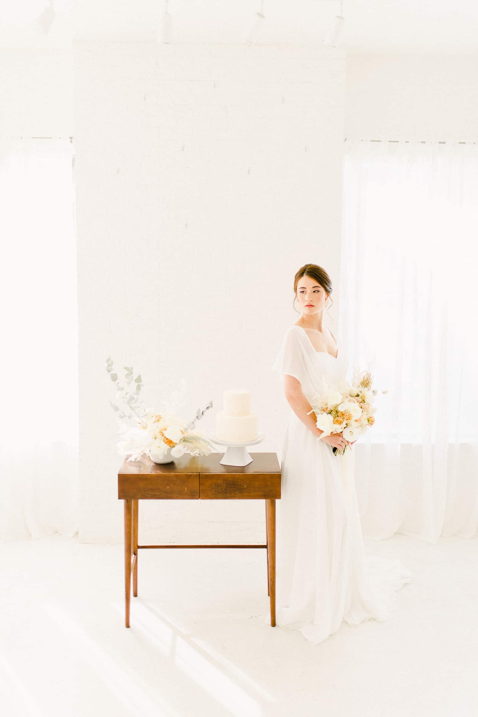 Bride standing in front if Modern wooden wedding cake table with minimalist neutral flowers