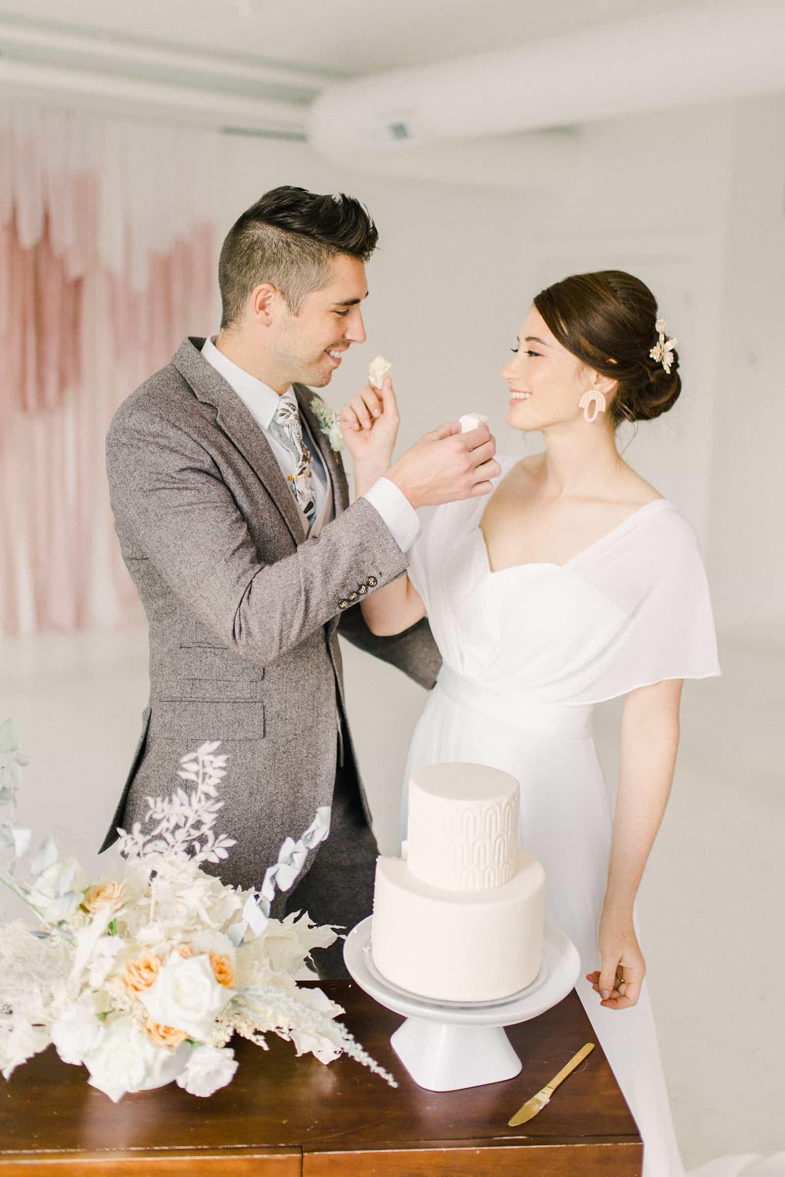 Bride and groom feed each other wedding cake, modern wedding