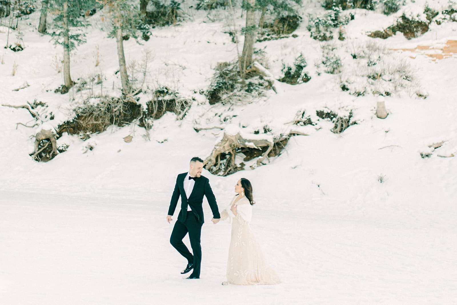 Bride and groom walking in the snow at Tibble Fork Reservoir in American Fork Canyon, Utah