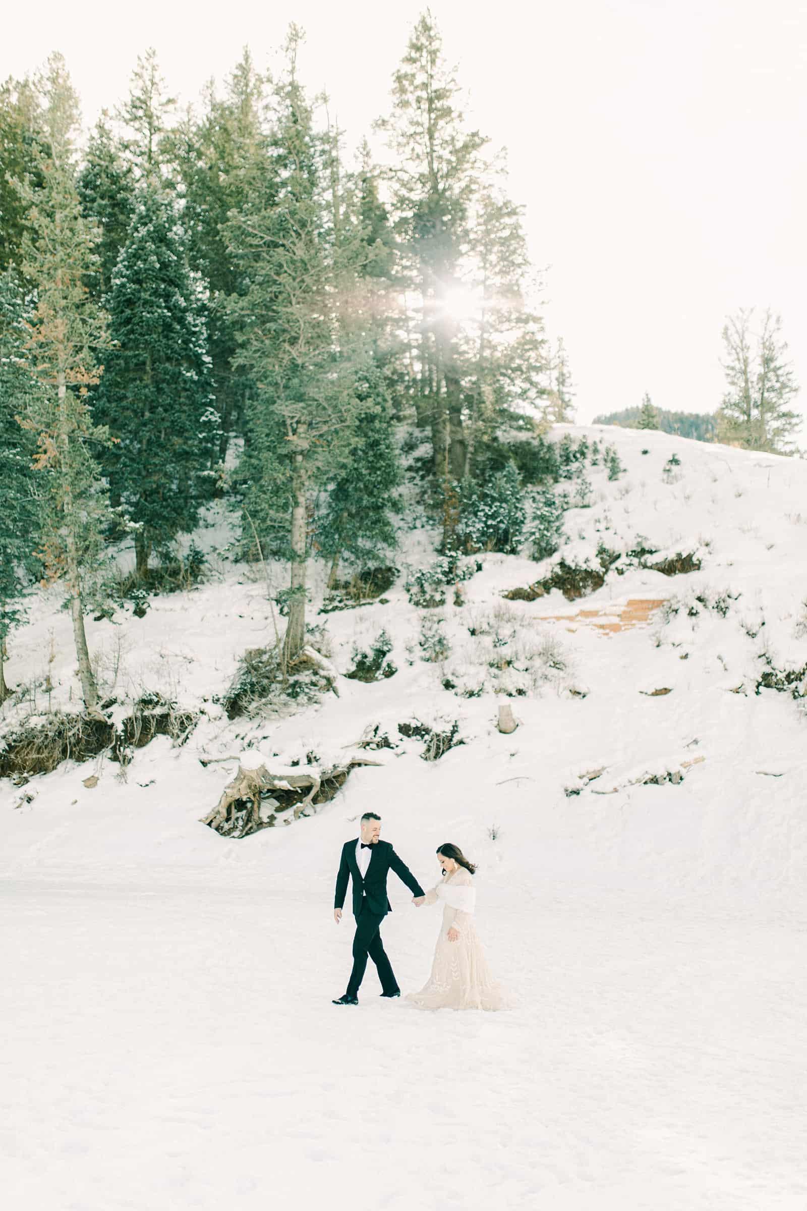 Bride and groom walking in snowy winter mountains of Utah
