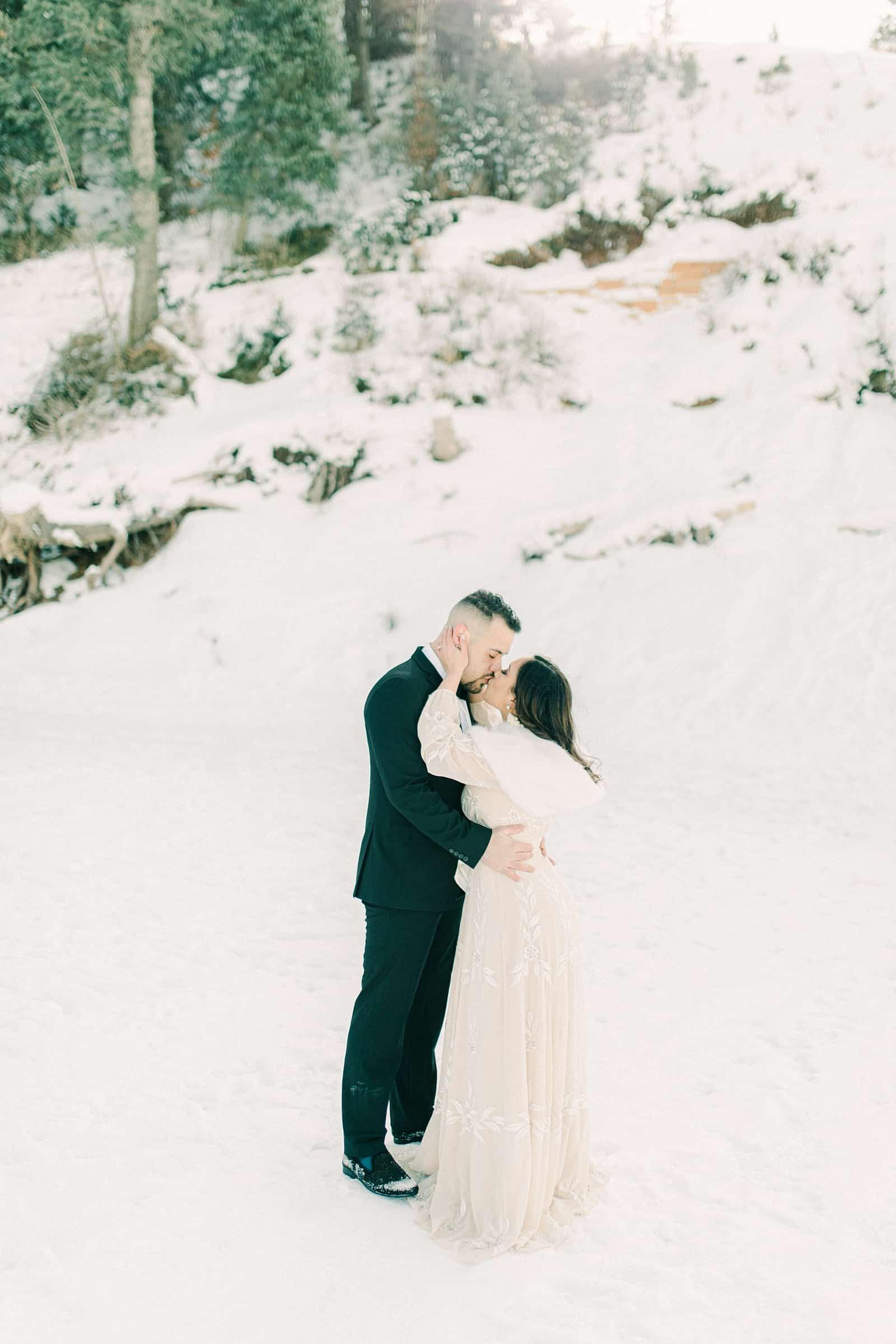 Bride and groom snowy winter mountains of Utah