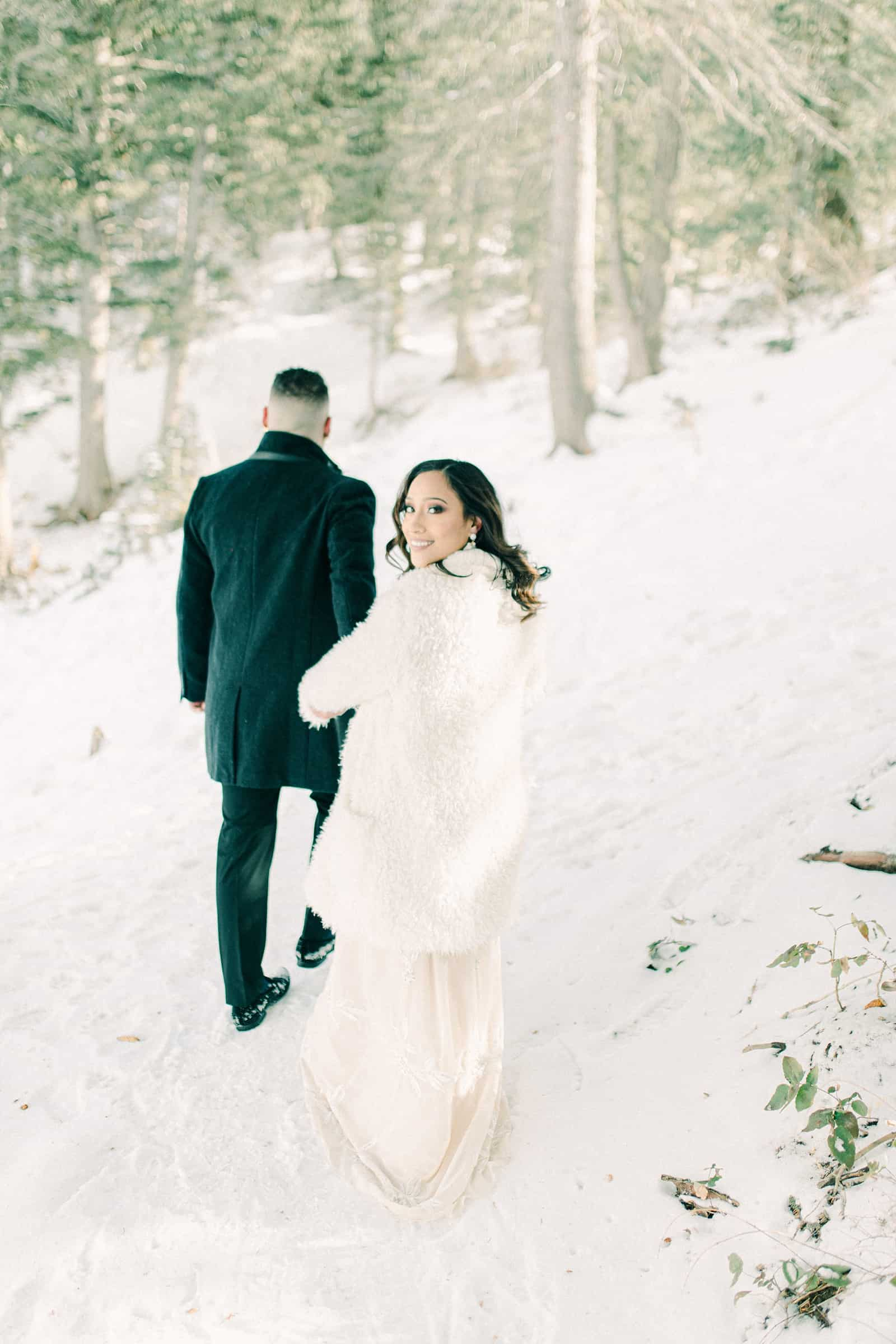 Outfits for winter wedding engagement session, walking through snowy forest